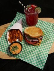 """La hamburguesa de Spicoli recibe su nombre de Jeff Spicoli de la película """"Fast Times at Ridgemont High"""". La hamburguesa de estilo californiano se muestra aquí con el jugo hippy de The Closet Vegan, las papas fritas y la salsa especial."""