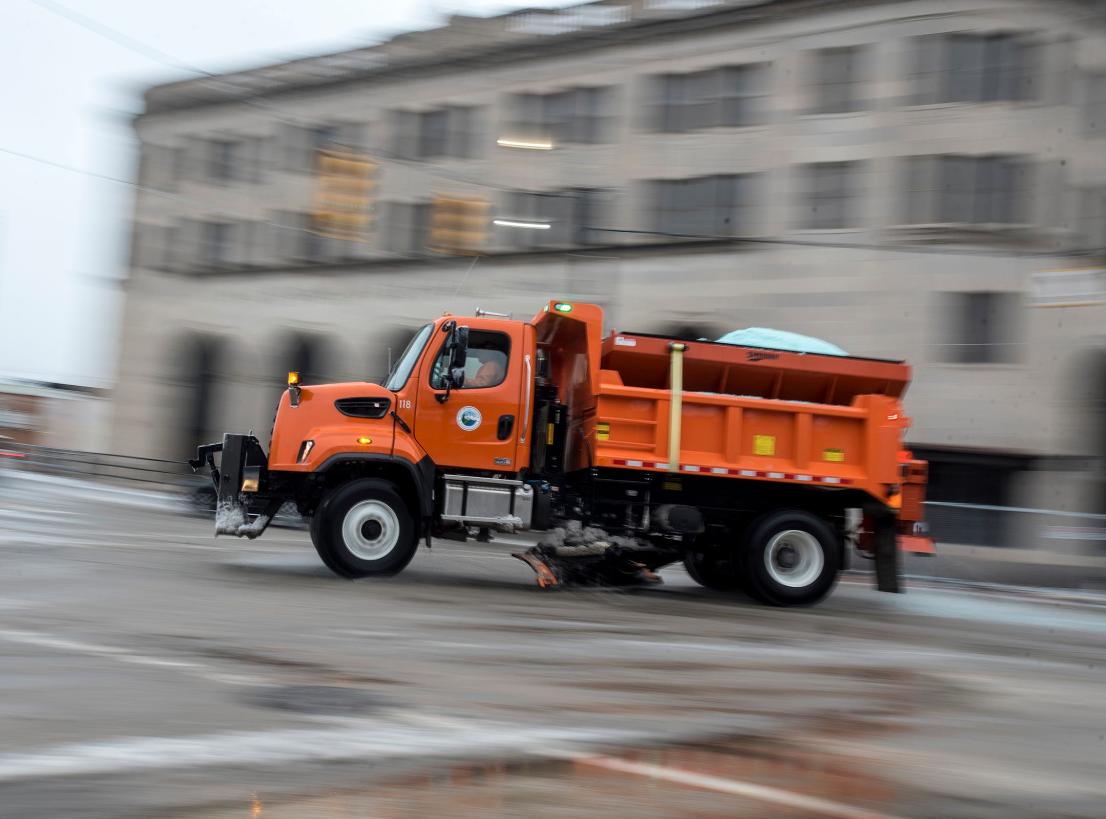 A salt truck turns west onto Water Street from Military Street Wednesday, Feb. 6, 2019 in downtown Port Huron.