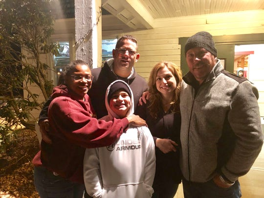 Jeff Heck (right) poses alongside friends and Arlington community members, including Jocelyn Greene-Fox (left) who attended a Feb. 5 prayer vigil for his son, Austin Heck, who's battling cancer.