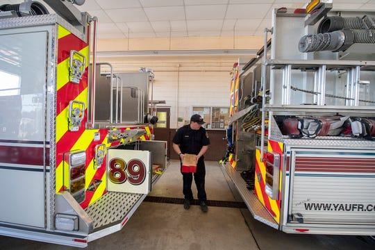 Firefighter Brandon Banks takes cribbing from the engine at right and sees how it will fit in the new 2019 Spartan engine at left at York Area United Fire & Rescue's Victory Fire Co. No. 2 in Spring Garden Township. The fire company has three new engines.
