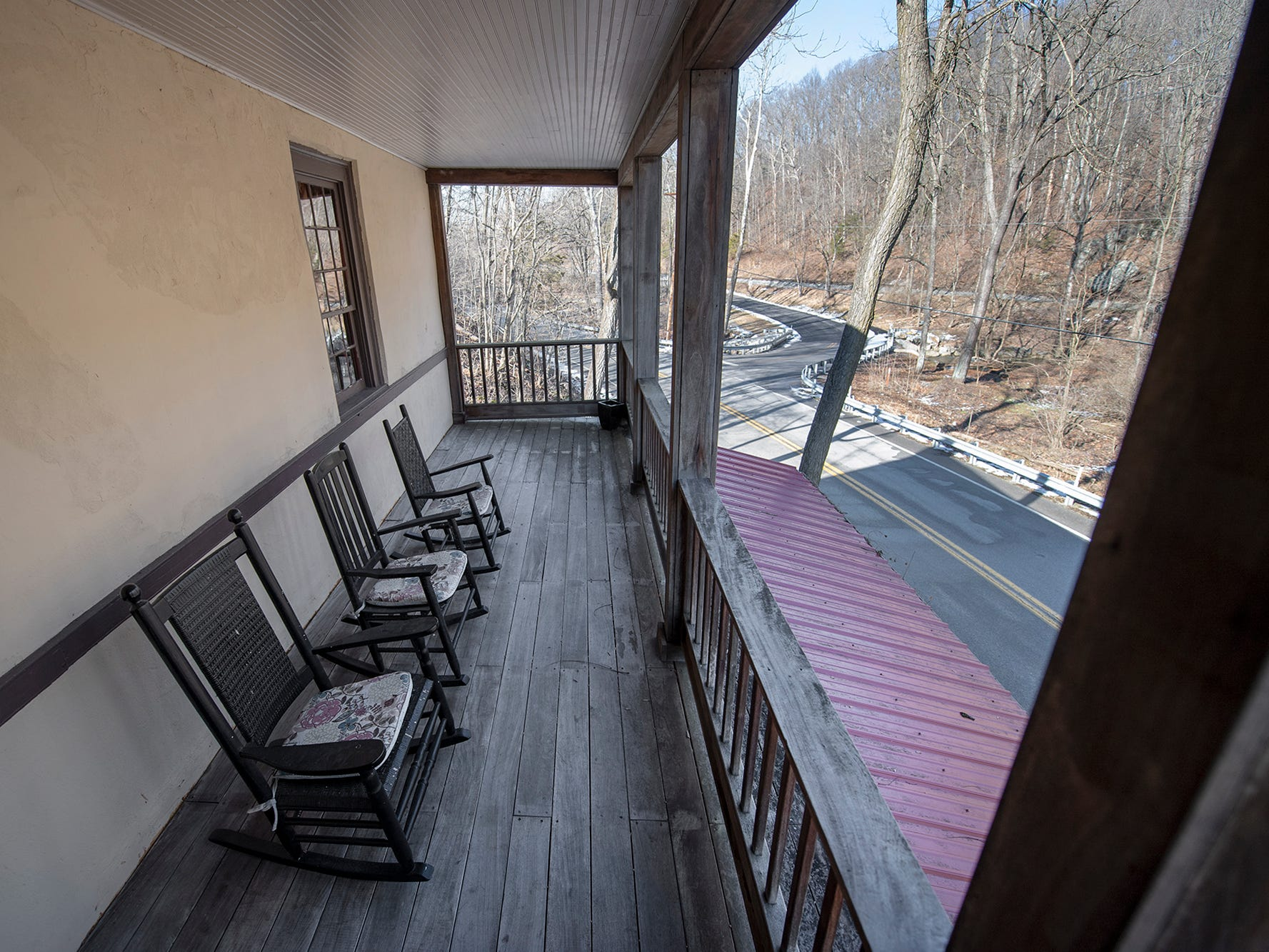 A porch overlooks the hillside from the grooms quarters. Notable wedding and event venue, the historic Stone Mill 1792 in York County, is for sale.