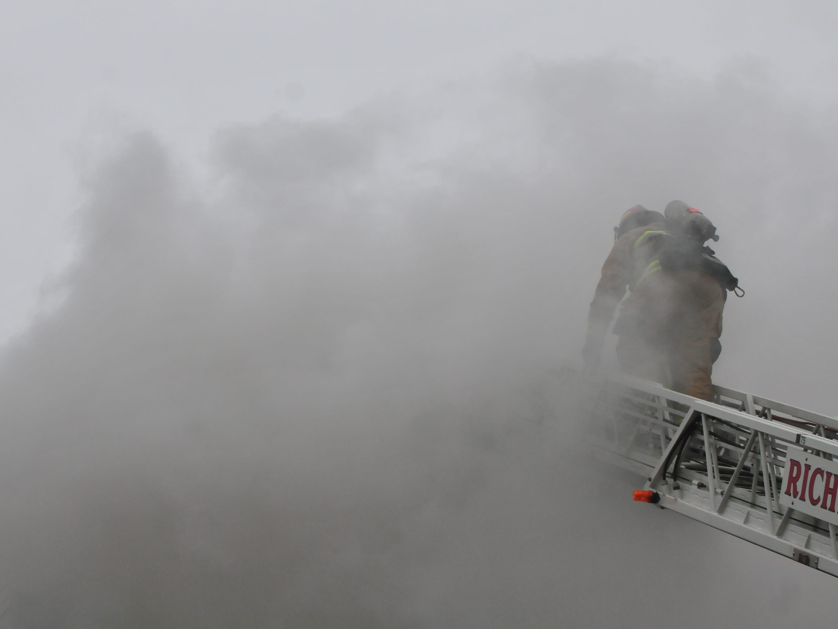 Richmond Fire Department personnel climbs into the smoke on an aerial ladder Wednesday.