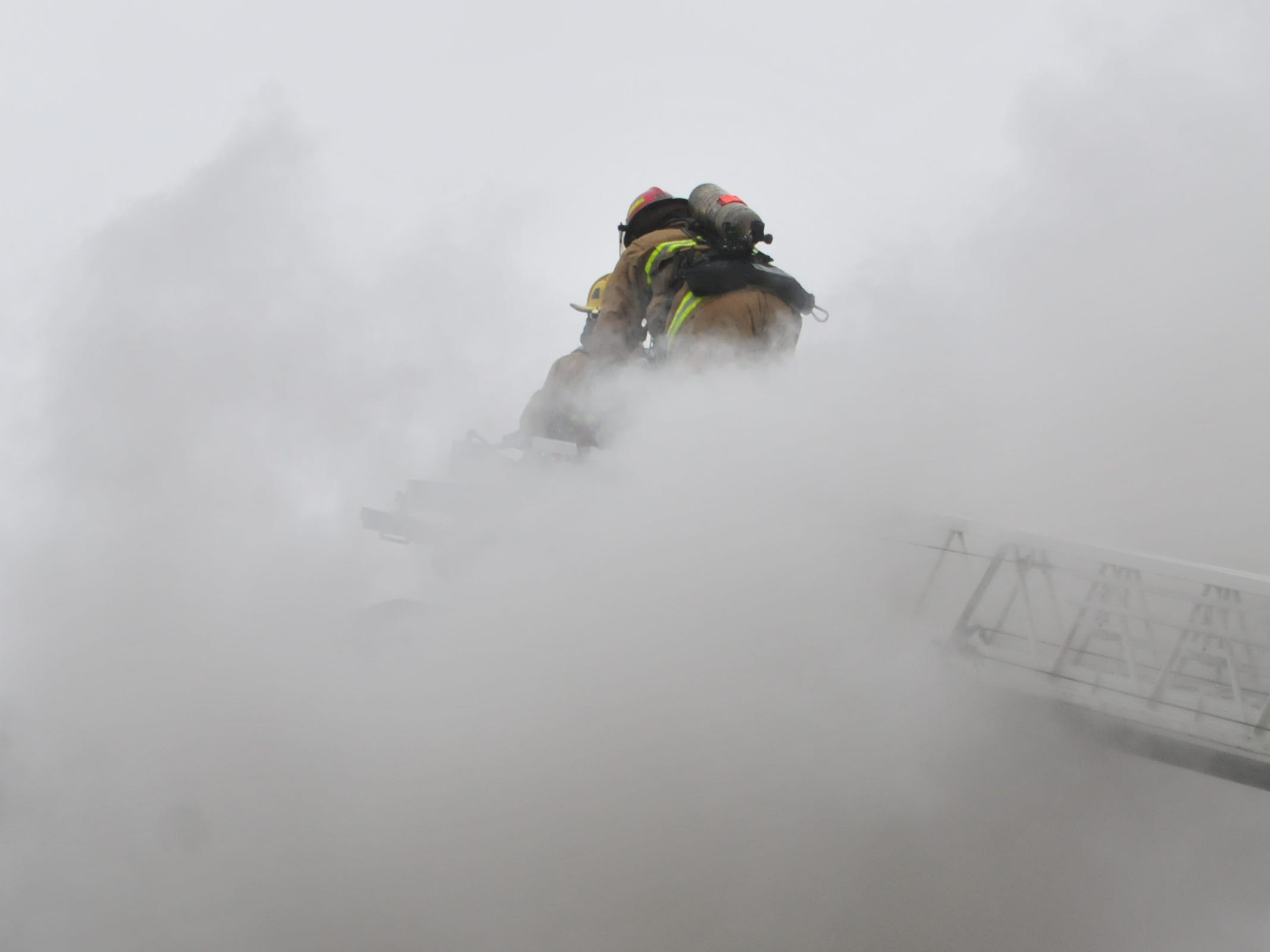 Richmond Fire Department personnel work on a aerial ladder Wednesday during a fire at 112 N. 18th St.
