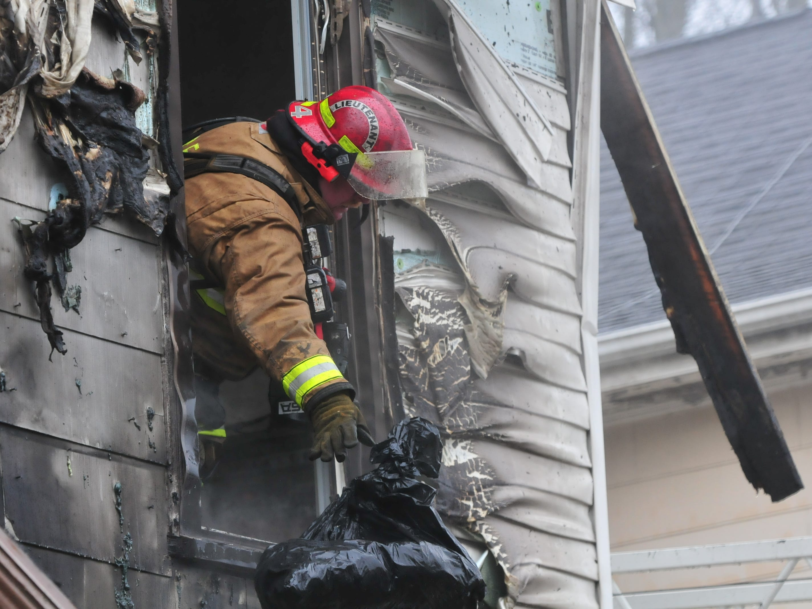 Richmond Fire Department personnel toss belongings out a window of 112 N. 18th St. during Wednesday's fire.