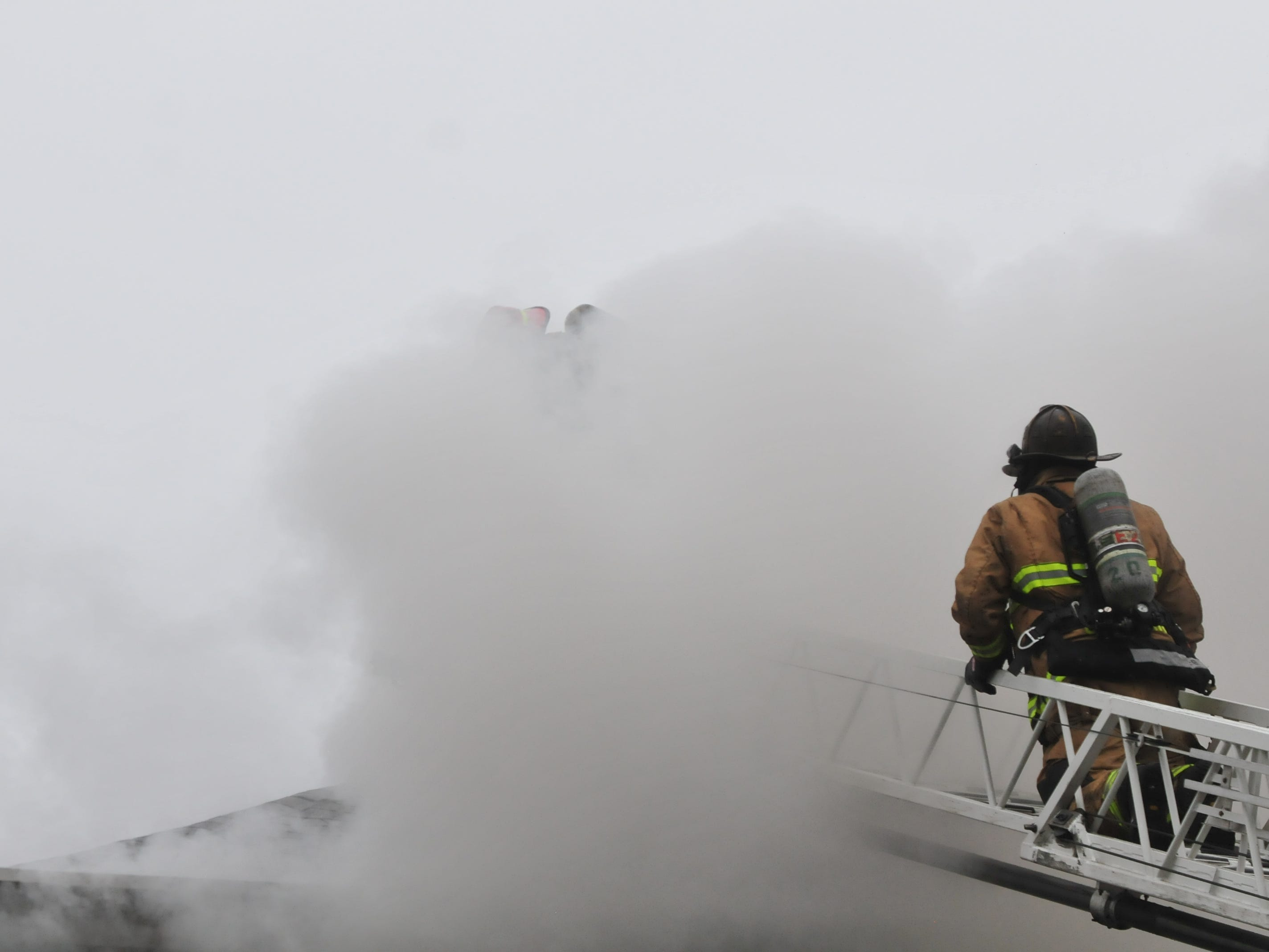 Smoke hides Richmond Fire Department personnel working from an aerial ladder Wednesday during a fire at 112 N. 18th St.