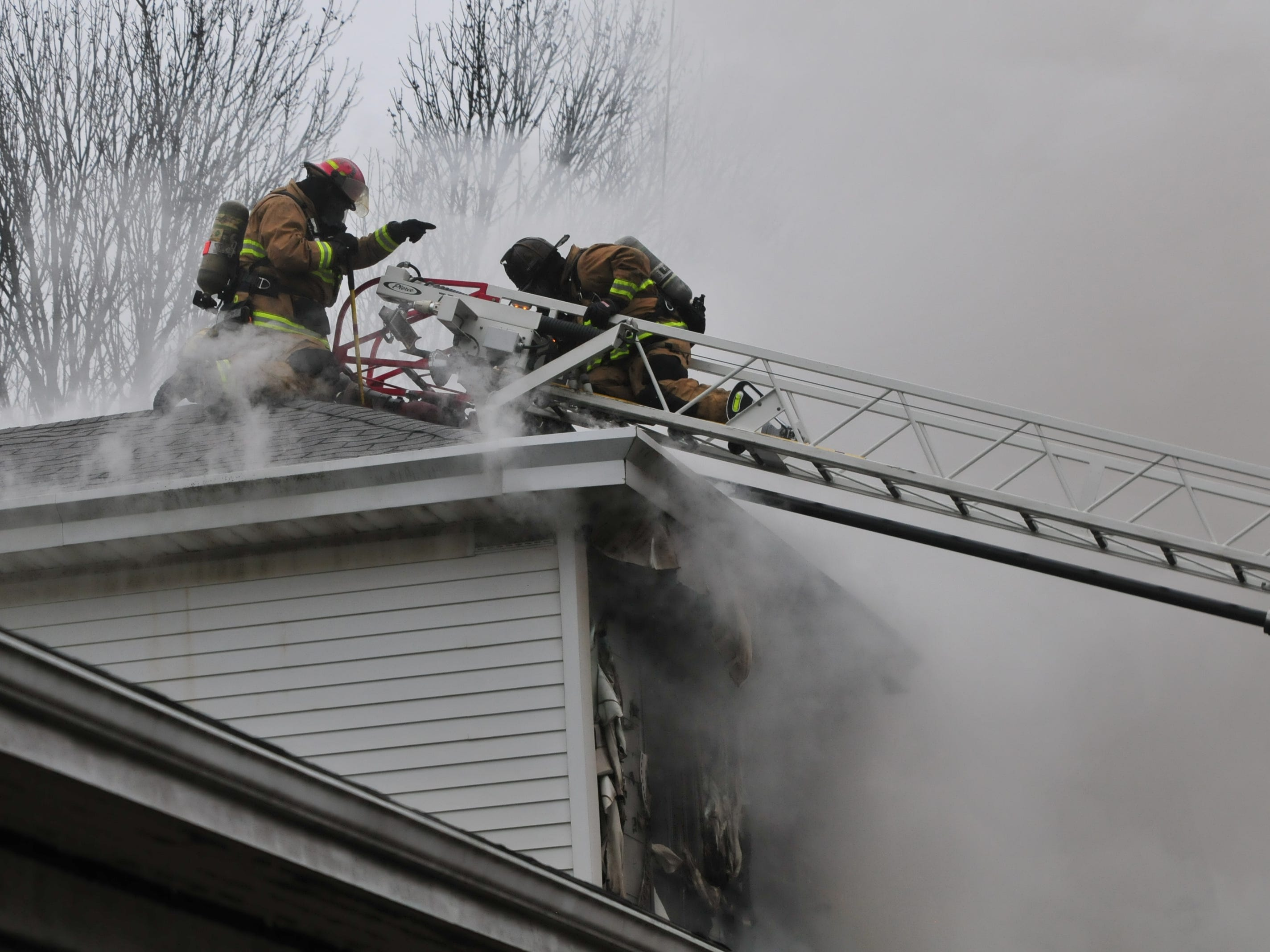 Richmond Fire Department personnel work on the roof Wednesday during a fire at 112 N. 18th St.