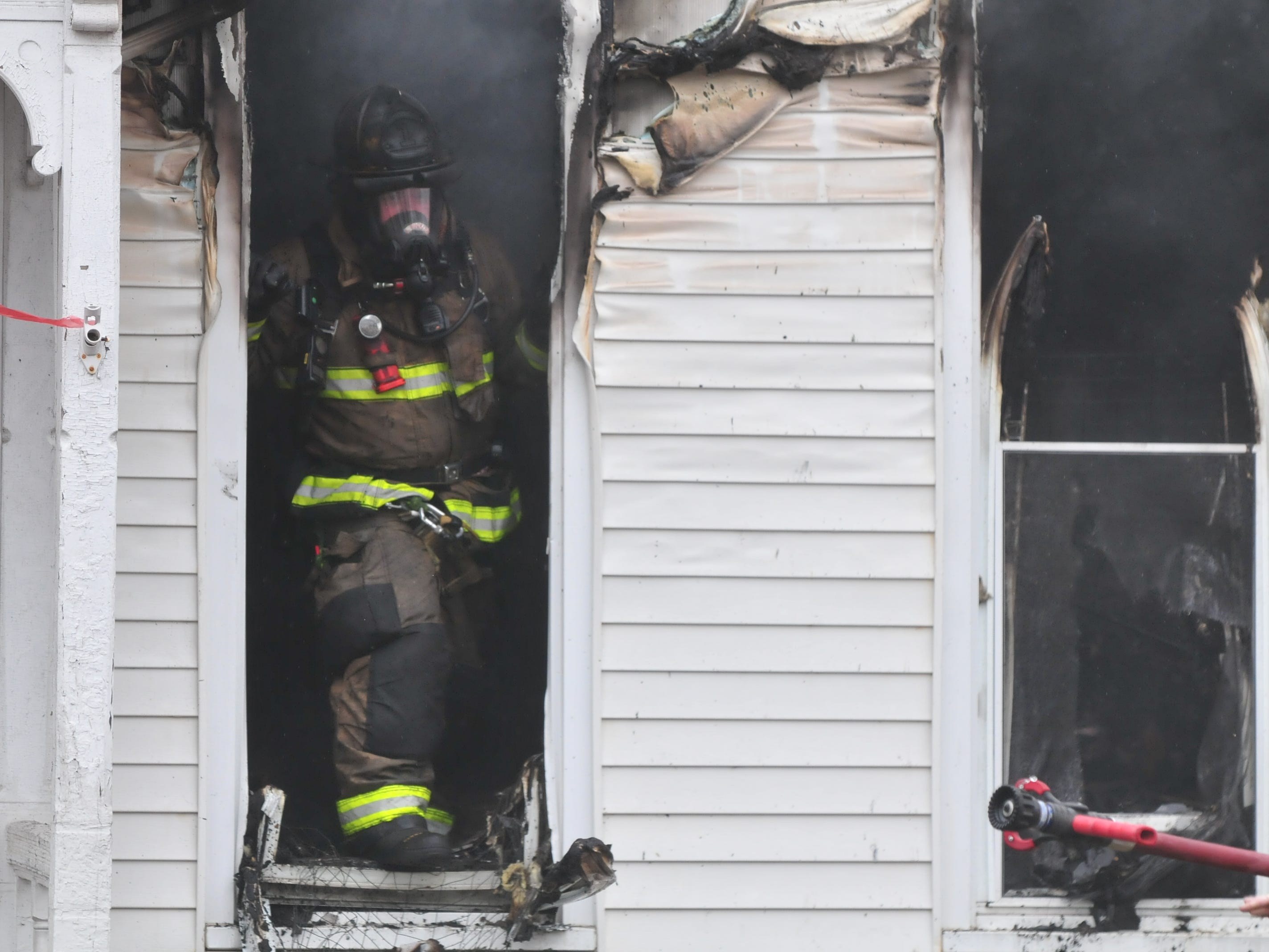 A firefighter waits for a hose line during a house fire Wednesday at 112 N. 18th St.