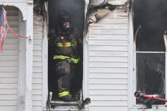 A firefighter waits for a hose line during a house fire in this file photo.