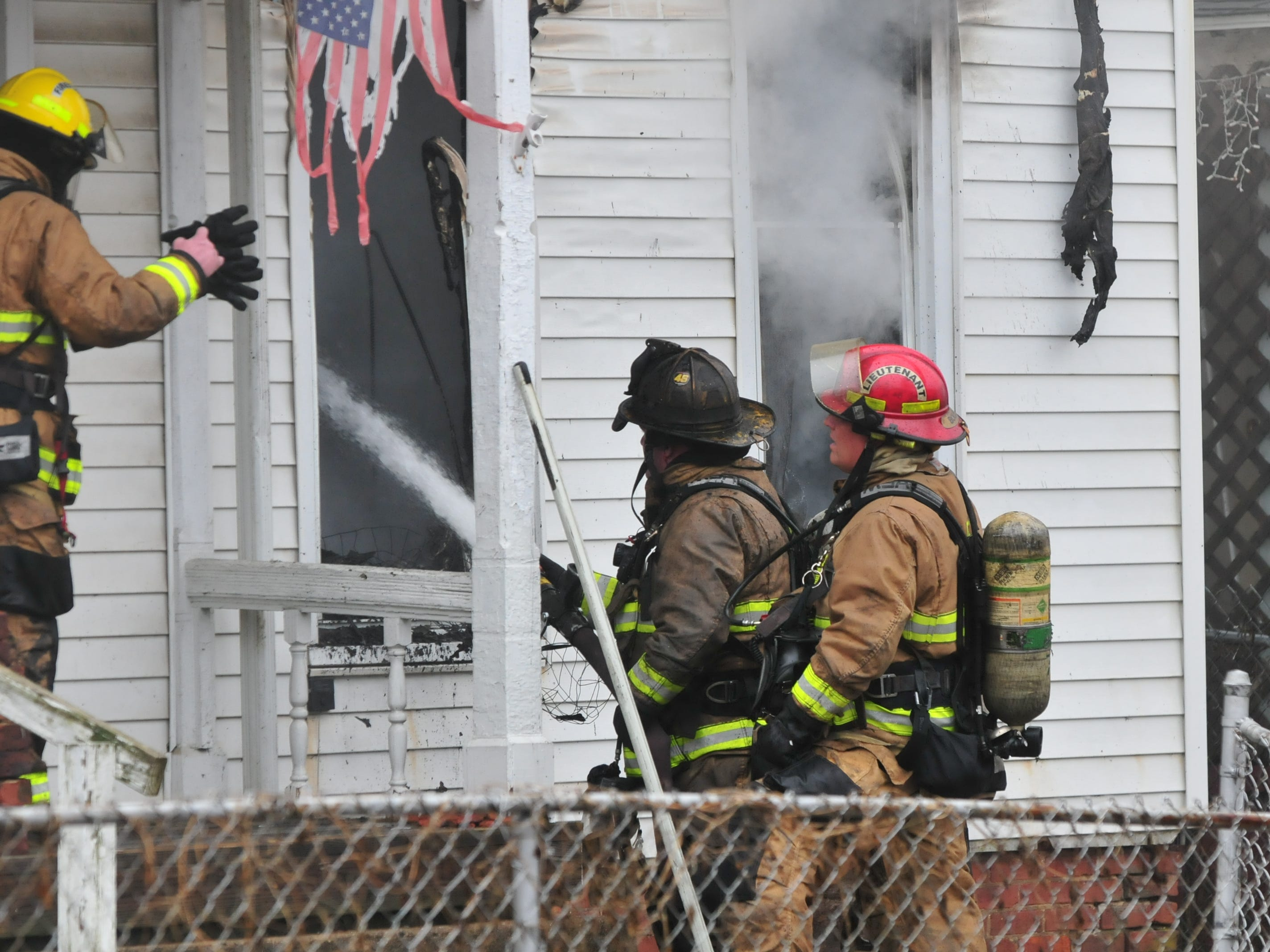 Richmond Fire Department personnel pours water into 112 N. 18th St. during Wednesday's fire.
