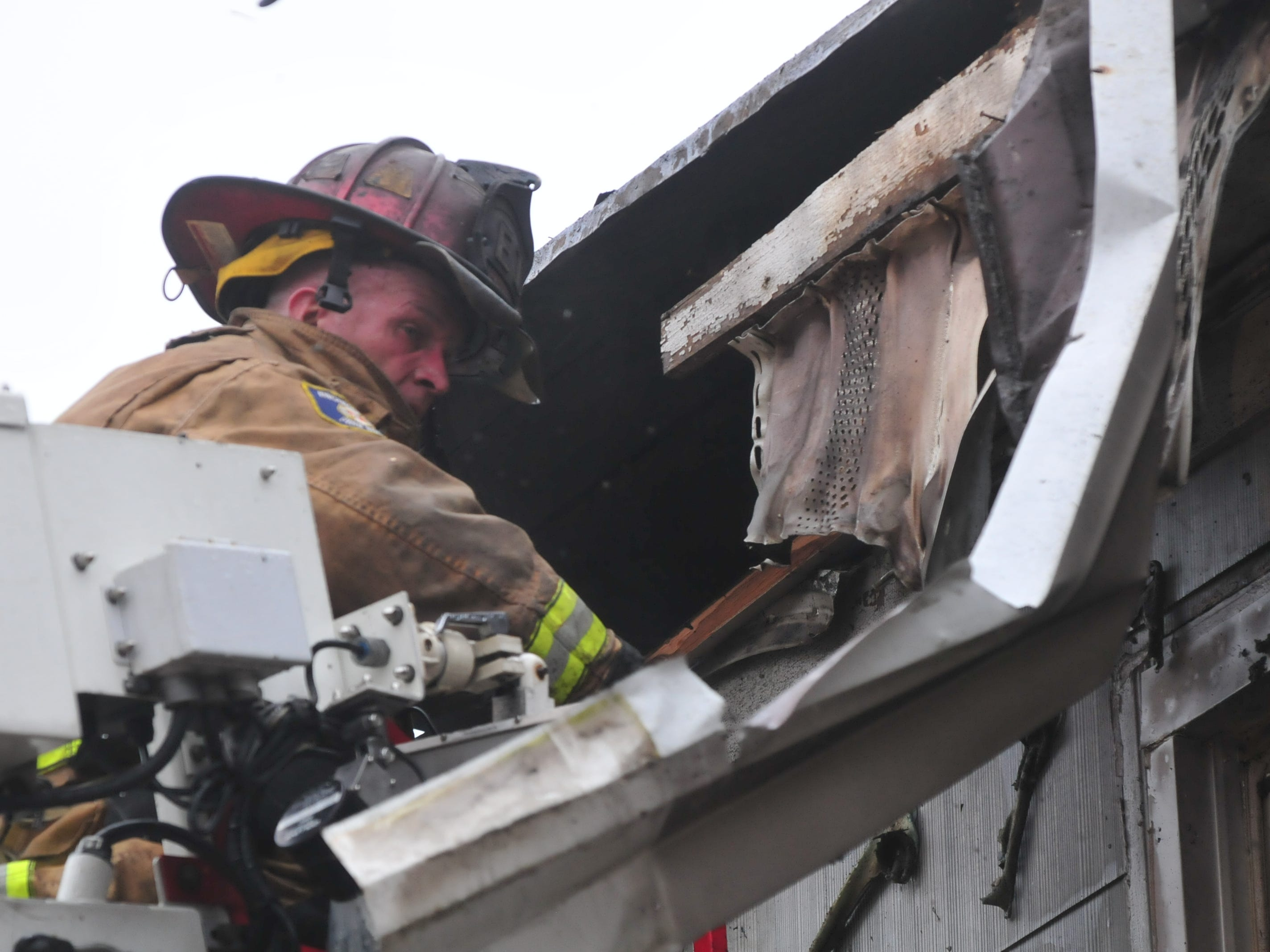 Lt. Kyle George works to access the final areas of fire Wednesday at 112 N. 18th St.