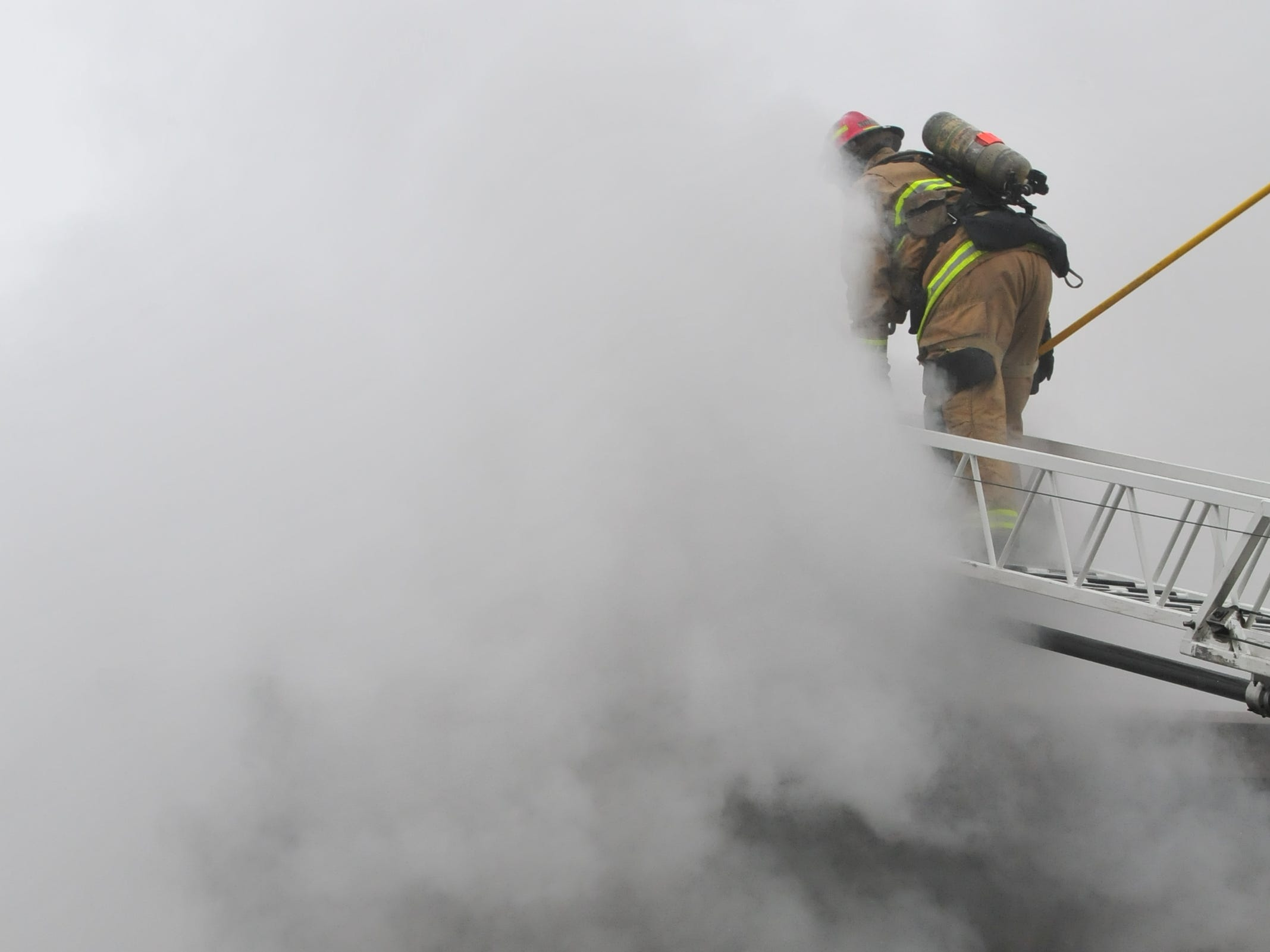 Richmond Fire Department personnel access the roof with an aerial ladder Wednesday during a fire at 112 N. 18th St.