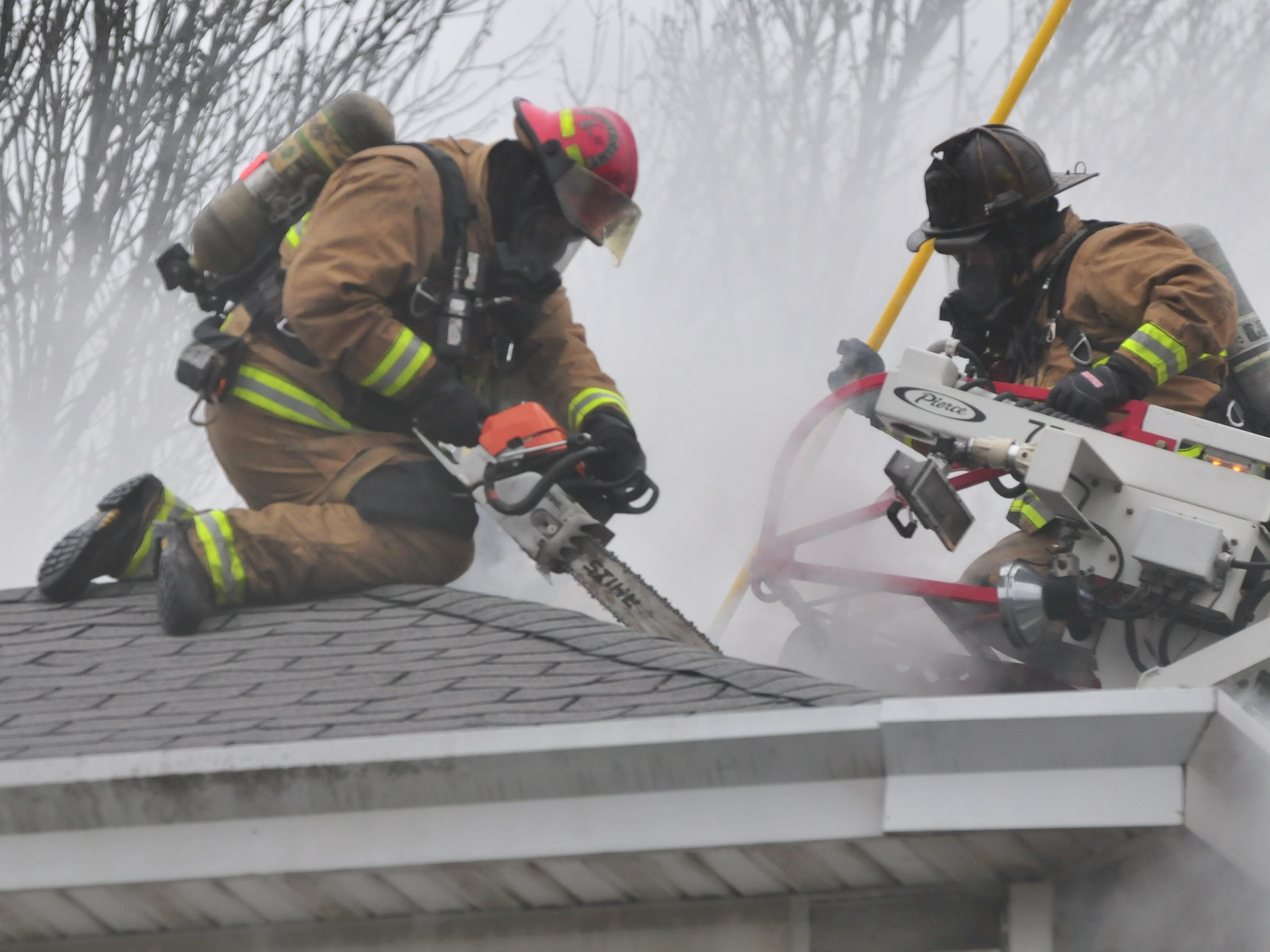 A chain saw helps cut ventilation holes in the roof Wednesday during a fire at 112 N. 18th St.