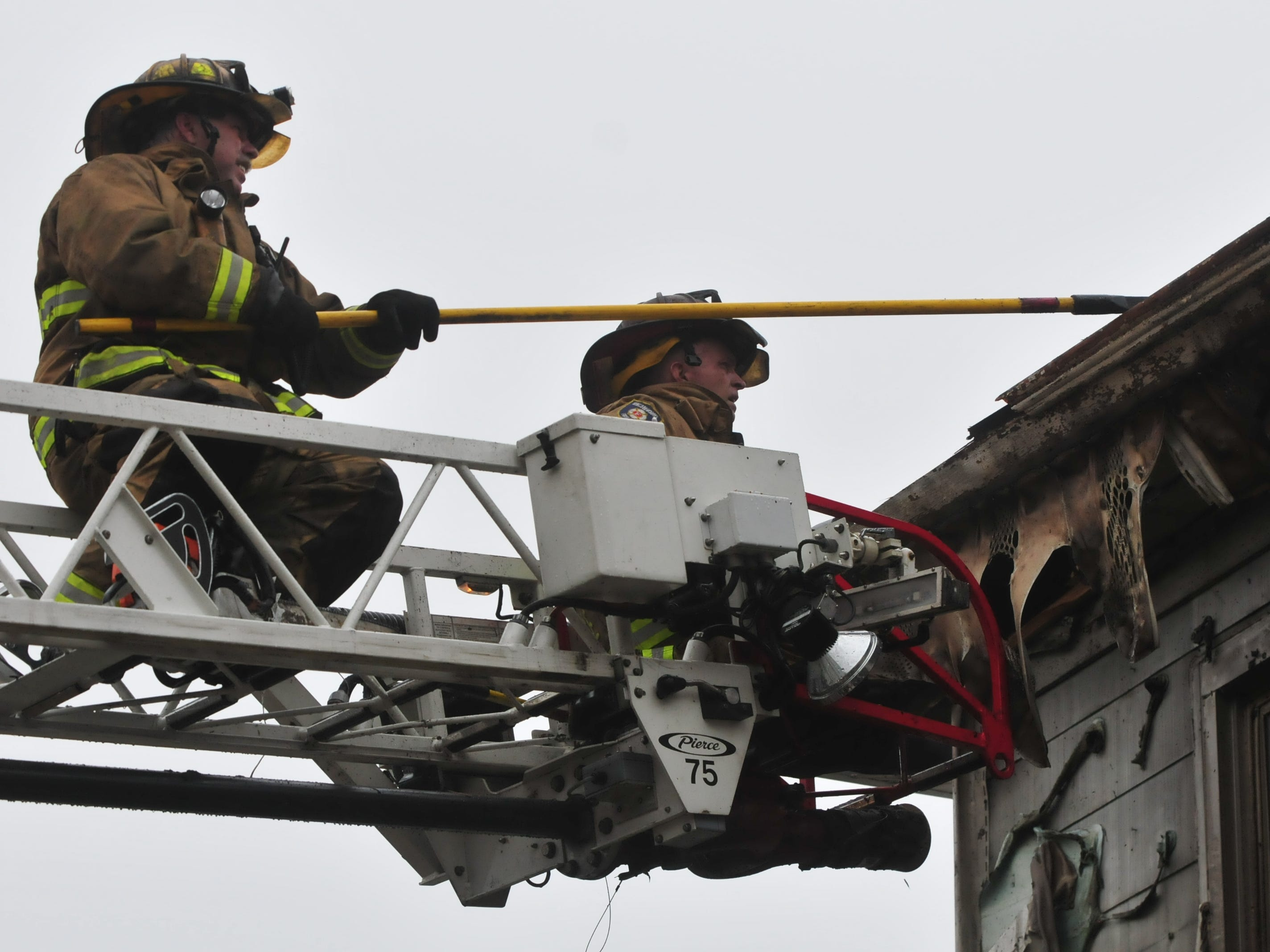 Firefighter Jeff Glenn and Lt. Kyle George pull down parts of the house at 112 N. 18th St. to access the final areas of fire Wednesday.
