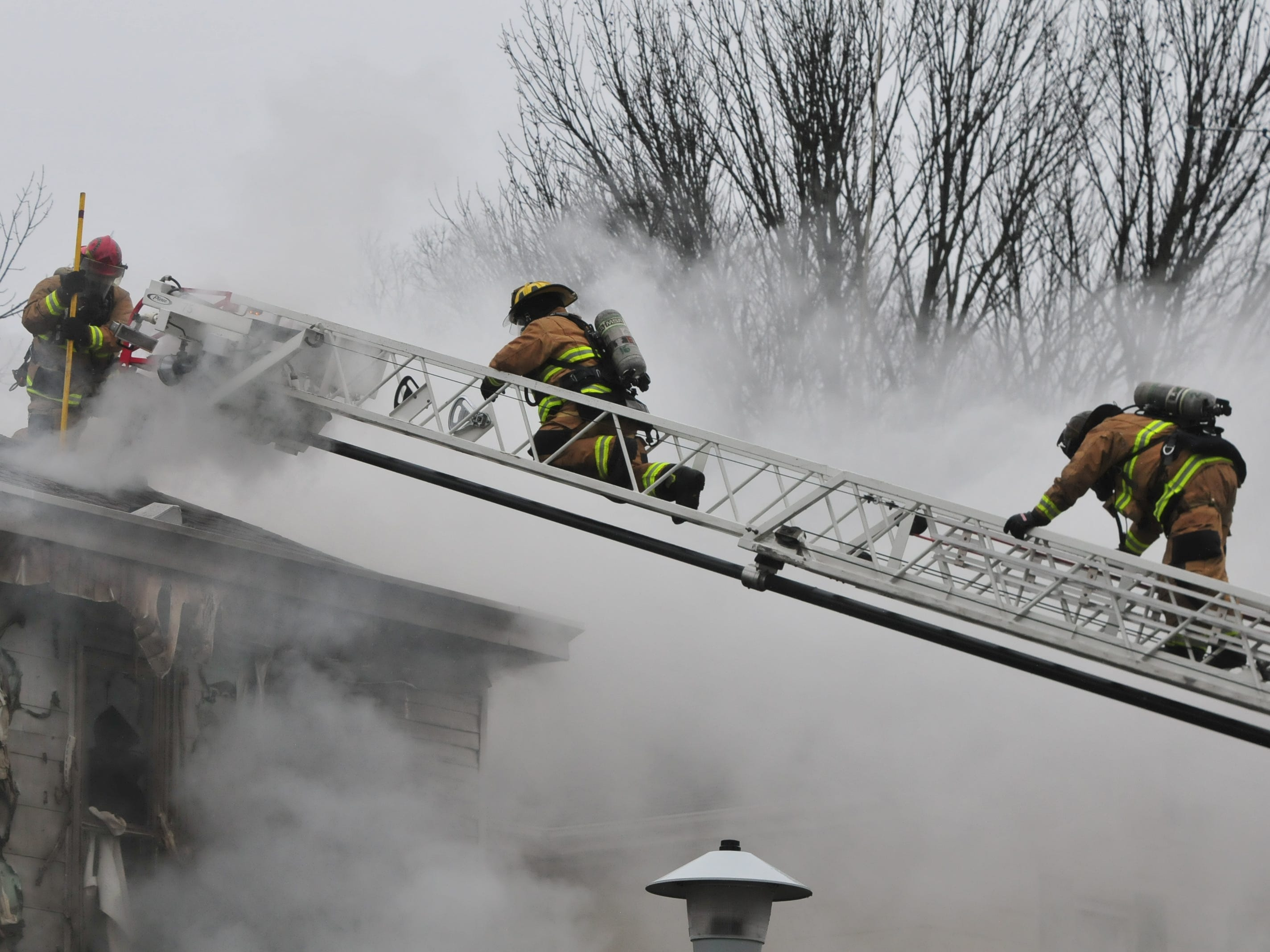 Richmond Fire Department personnel works with an aerial ladder Wednesday during a fire at 112 N. 18th St.