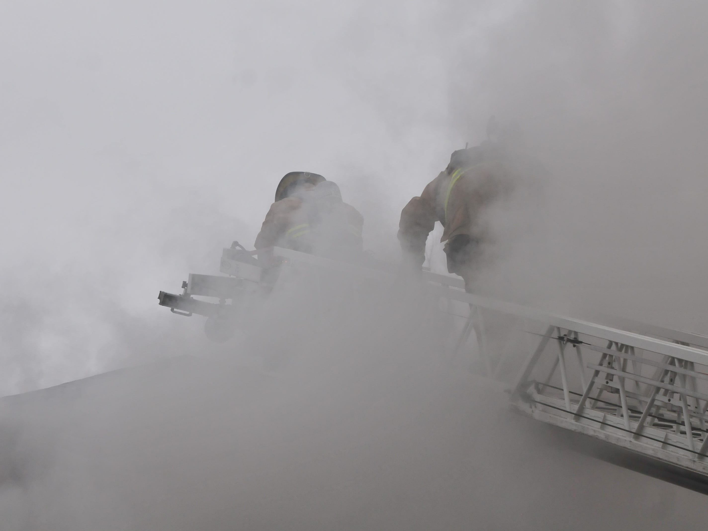 Richmond Fire Department personnel access the roof to cut ventilation holes Wednesday during a fire at 112 N. 18th St.