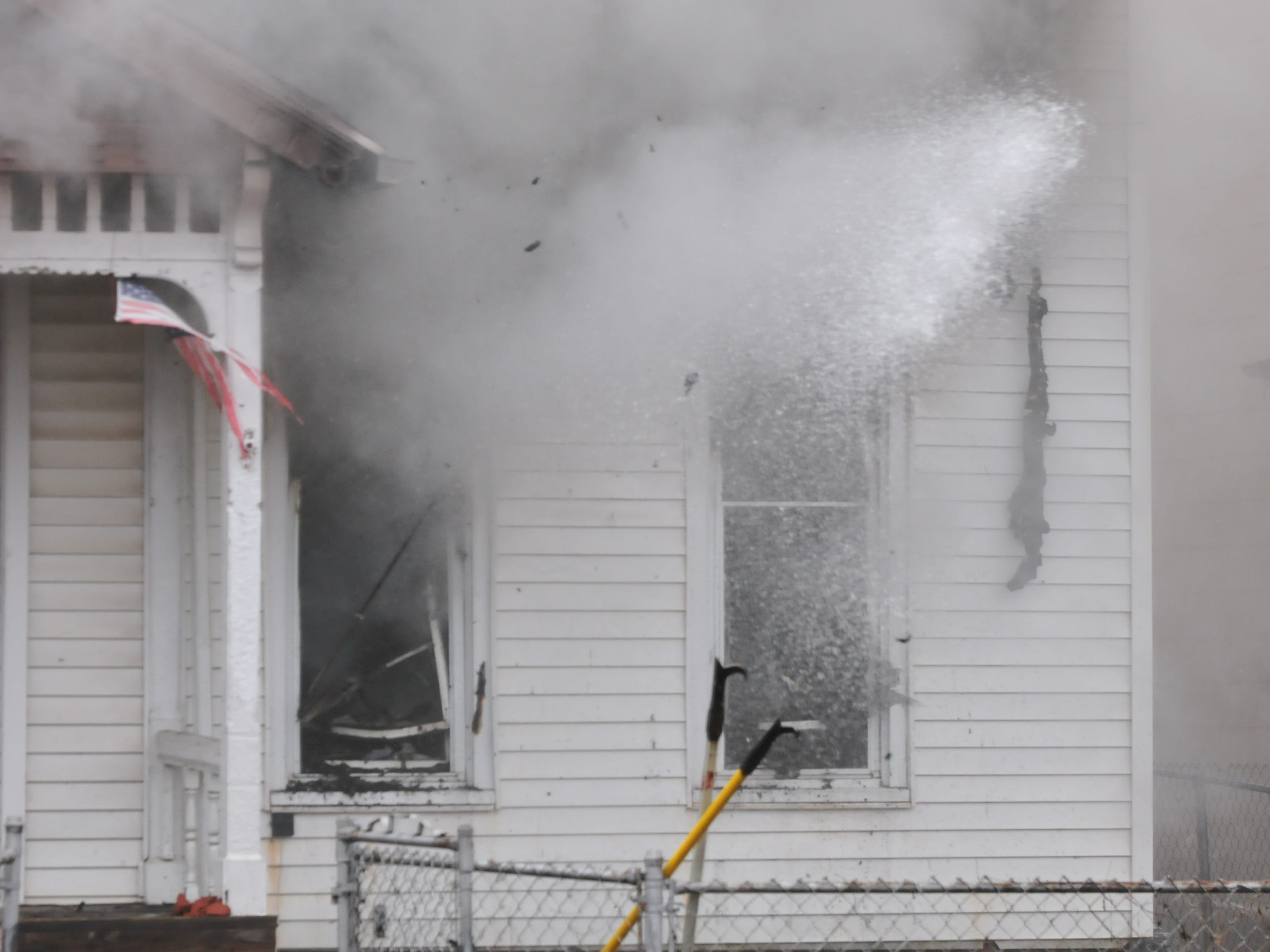 Water flies from a broken-out window as Richmond Fire Department personnel sprays a fire Wednesday inside 112 N. 18th St.