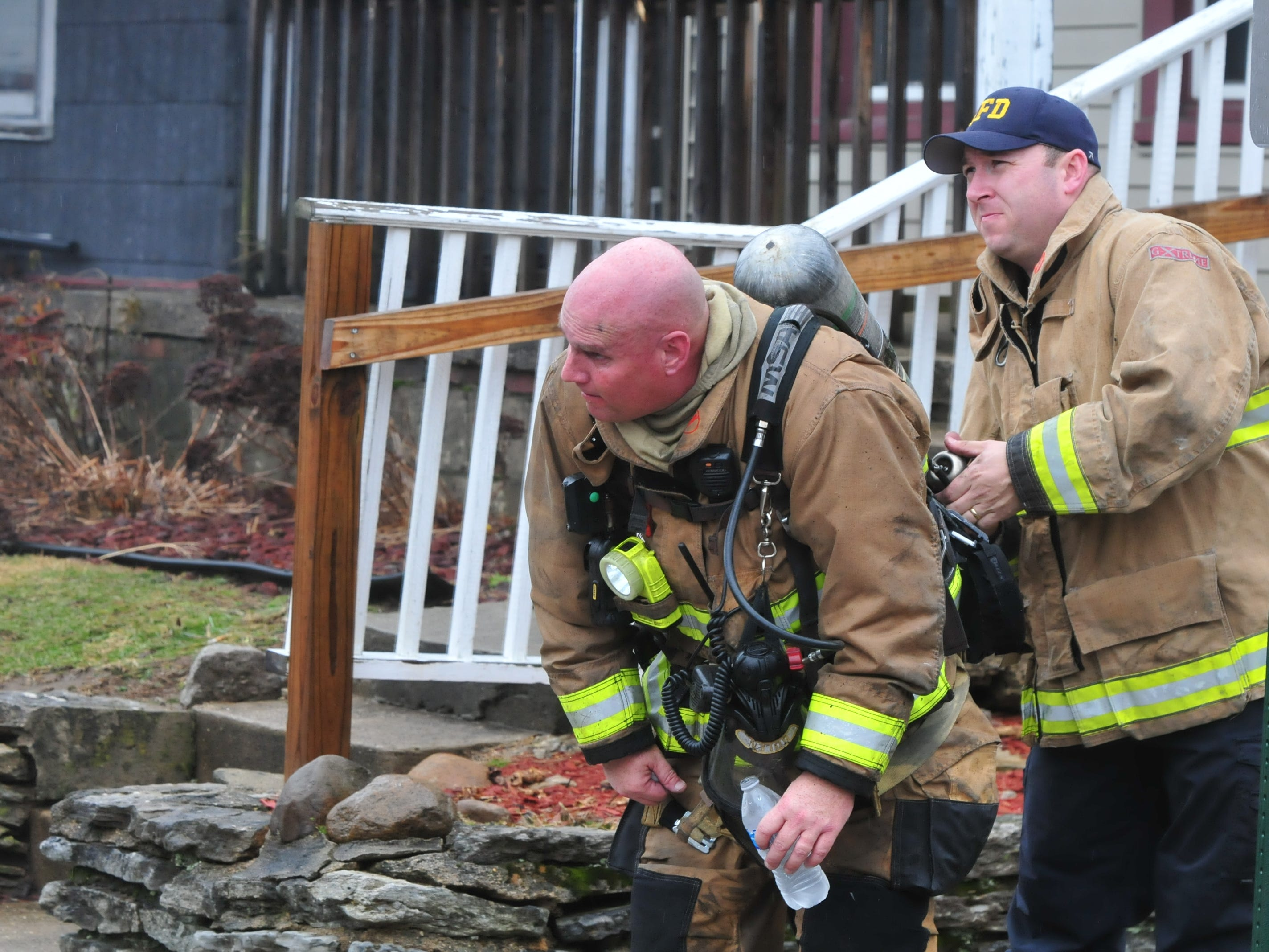 Chief of Fire Prevention Mike Davis helps change an oxygen tank Wednesday during a fire at 112 N. 18th St.