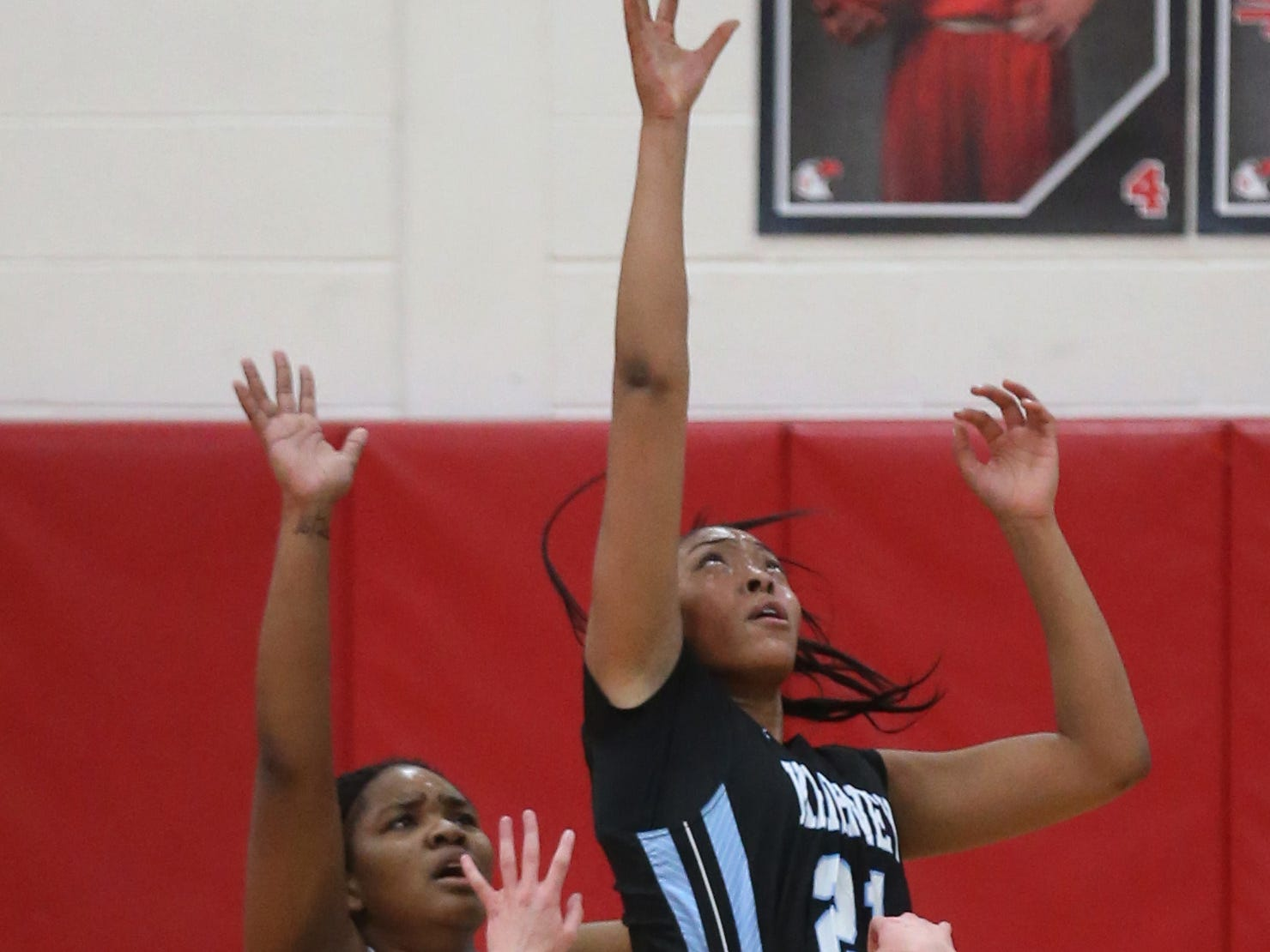 The ball is lobbed into Kearney's Saniaa Wilson in the low post over Penfield's Nyara Simmons, left, and Baylee Teal, right.
