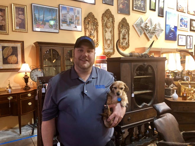 Joe Battaglia, 30, stands with Tucker in the 4,000-square-foot Estate Marketplace.He opened the Parma shop Dec. 1 with Jeff DelCorvo.