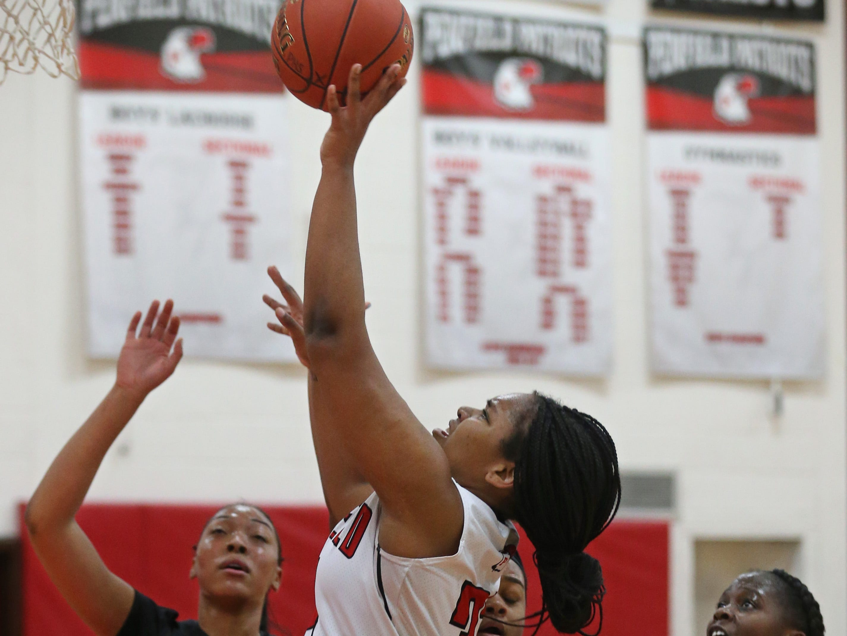 Penfield's Nyara Simmons drives in for two points past a trio of Kearney defenders.