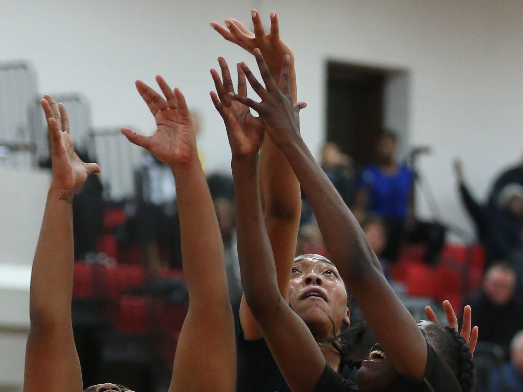 Kearney's Saniaa Wilson, center, gets a rebound over her teammate Lytoya Baker, right, and Penfield's Nyara Simmons, left.
