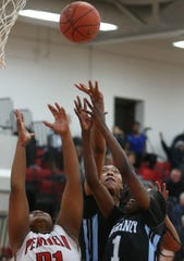 Kearney's Saniaa Wilson, center, gets a rebound over her teammate Lytoya Baker, right, and Penfield's Nyara Simmons, left.