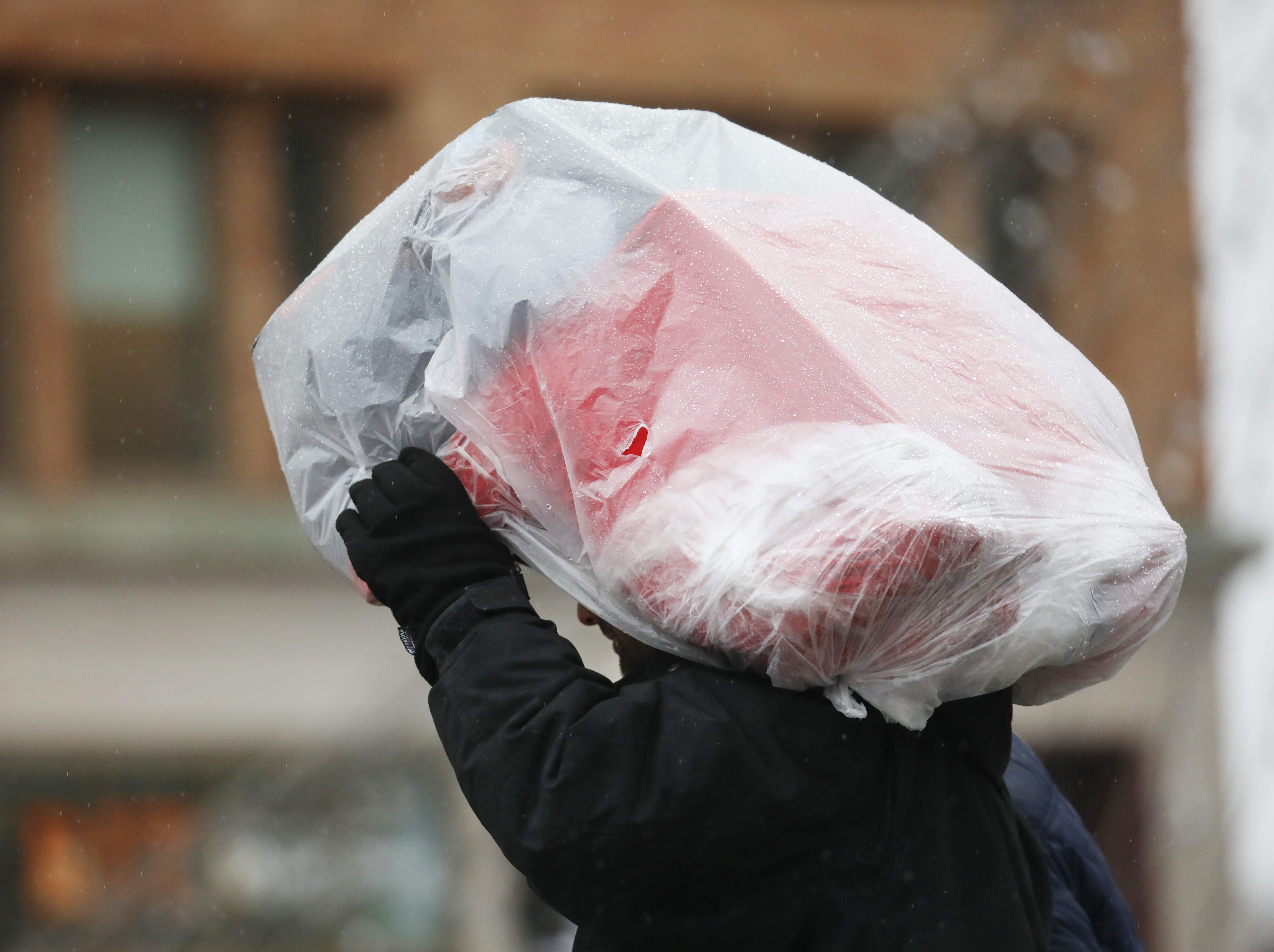 A man uses a toy car wrapped in plastic to cover his head from the rain in downtown Rochester.