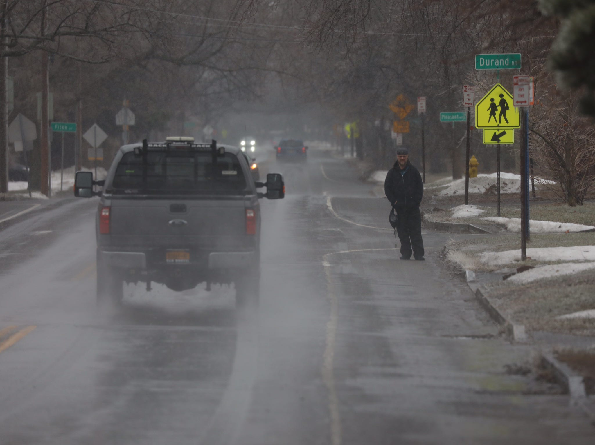 A commuter waits in the icy rain on Culver Road In Irondequoit.