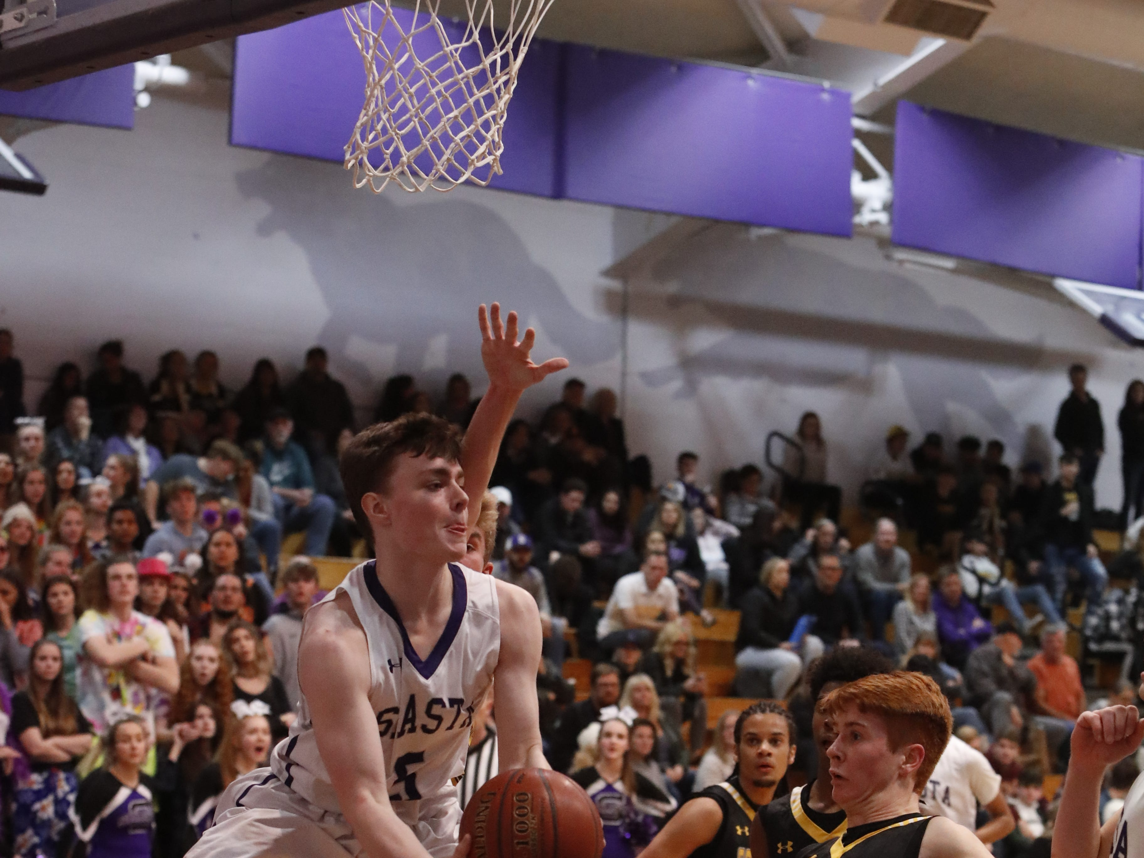 Shasta's Caden Cushman looks to pass the ball from under the rim during the second half of Shasta's 75-58 win over Enterprise on Tuesday, Feb. 5, 2019.