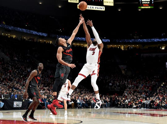 Miami Heat guard Dwyane Wade, right, hits a shot over Portland Trail Blazers guard CJ McCollum, center, as forward Al-Farouq Aminu watches during the first half of an NBA basketball game in Portland, Ore., Tuesday, Feb. 5, 2019.