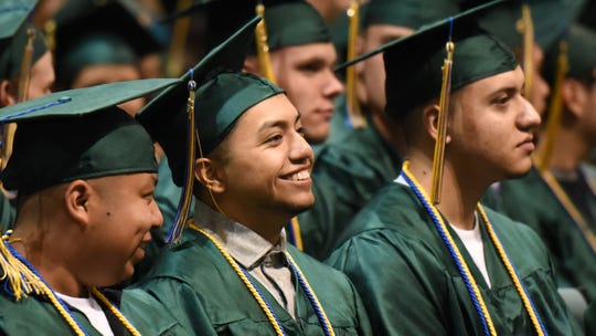 Graduates share a laugh during the 38th annual Douglas McKay High School commencement on Friday, June 9, 2017, at the Oregon State Fairgrounds Pavilion.