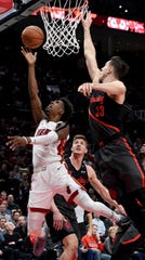 Miami Heat guard Josh Richardson, left, drives to the basket on Portland Trail Blazers center Jusuf Nurkic, right, during the first half of an NBA basketball game in Portland, Ore., Tuesday, Feb. 5, 2019.