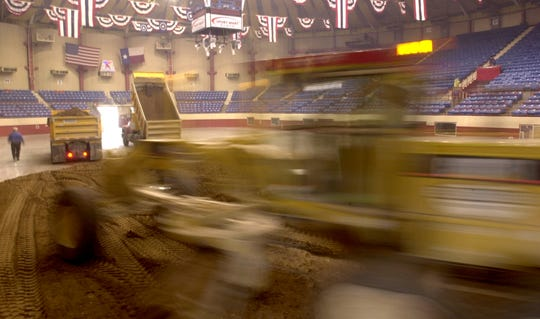 A Reece Albert motor grader operator spreads some of the 900 cubic yards of dirt required for the rodeo across the San Angelo Coliseum floor in this Standard-Times file photo from 2003.