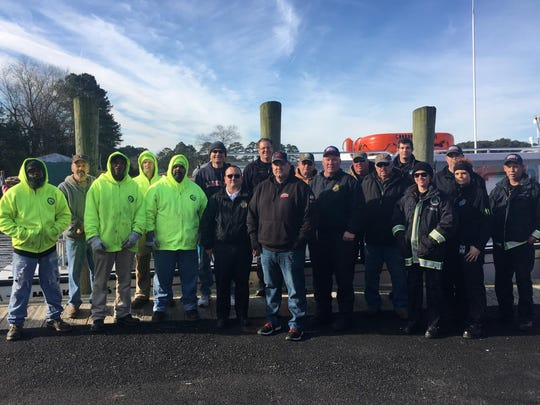 Accomack County employees pose for a photograph at the Onancock wharf during an operation to deliver 840 cases of drinking water to Tangier, after a water line broke on the island.