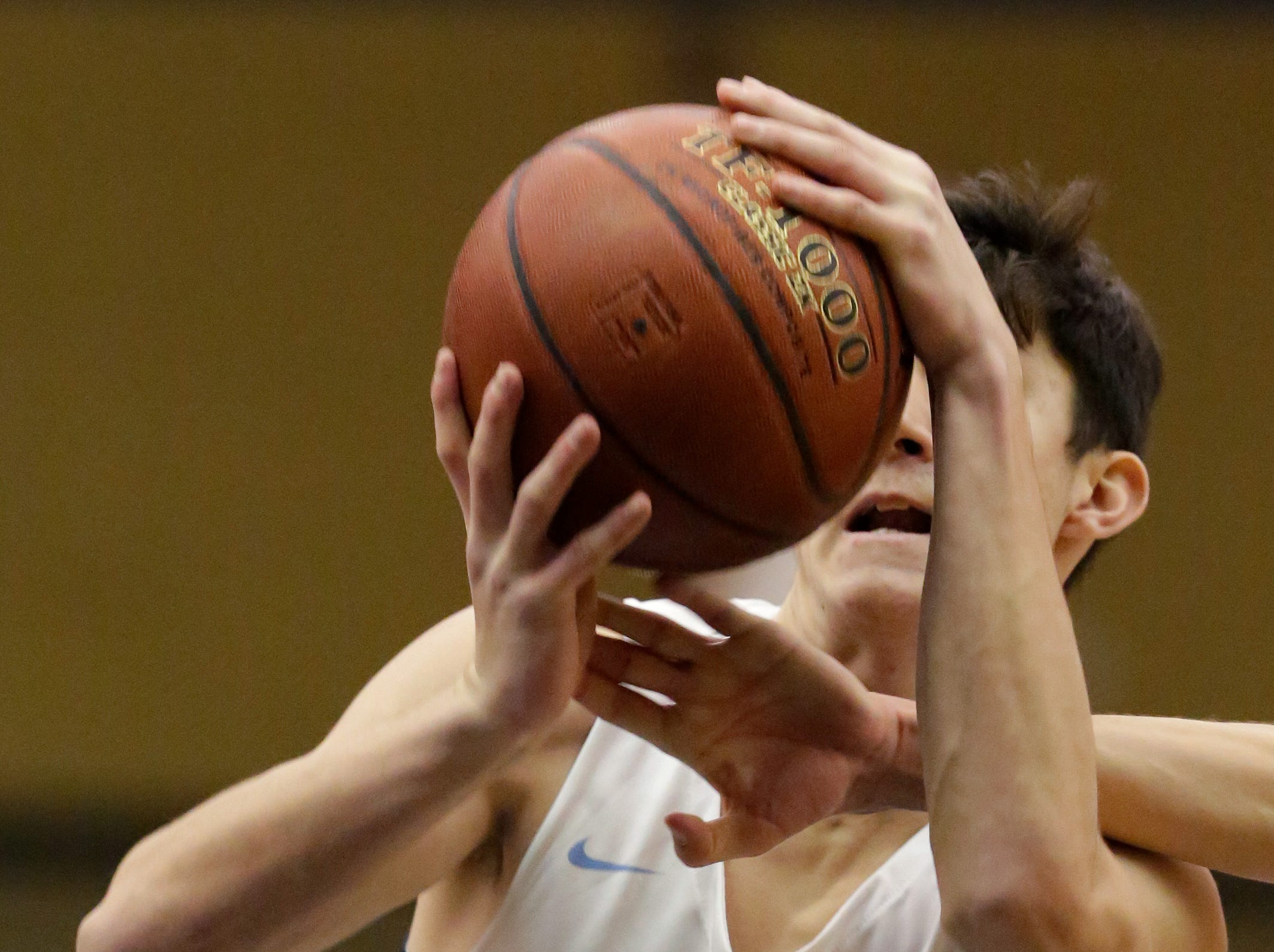 Sheboygan North's Austin Thyes (5) tries to aim a shot in a tangle of arms against Green Bay Southwest, Tuesday, February 5, 2019, in Sheboygan, Wis.