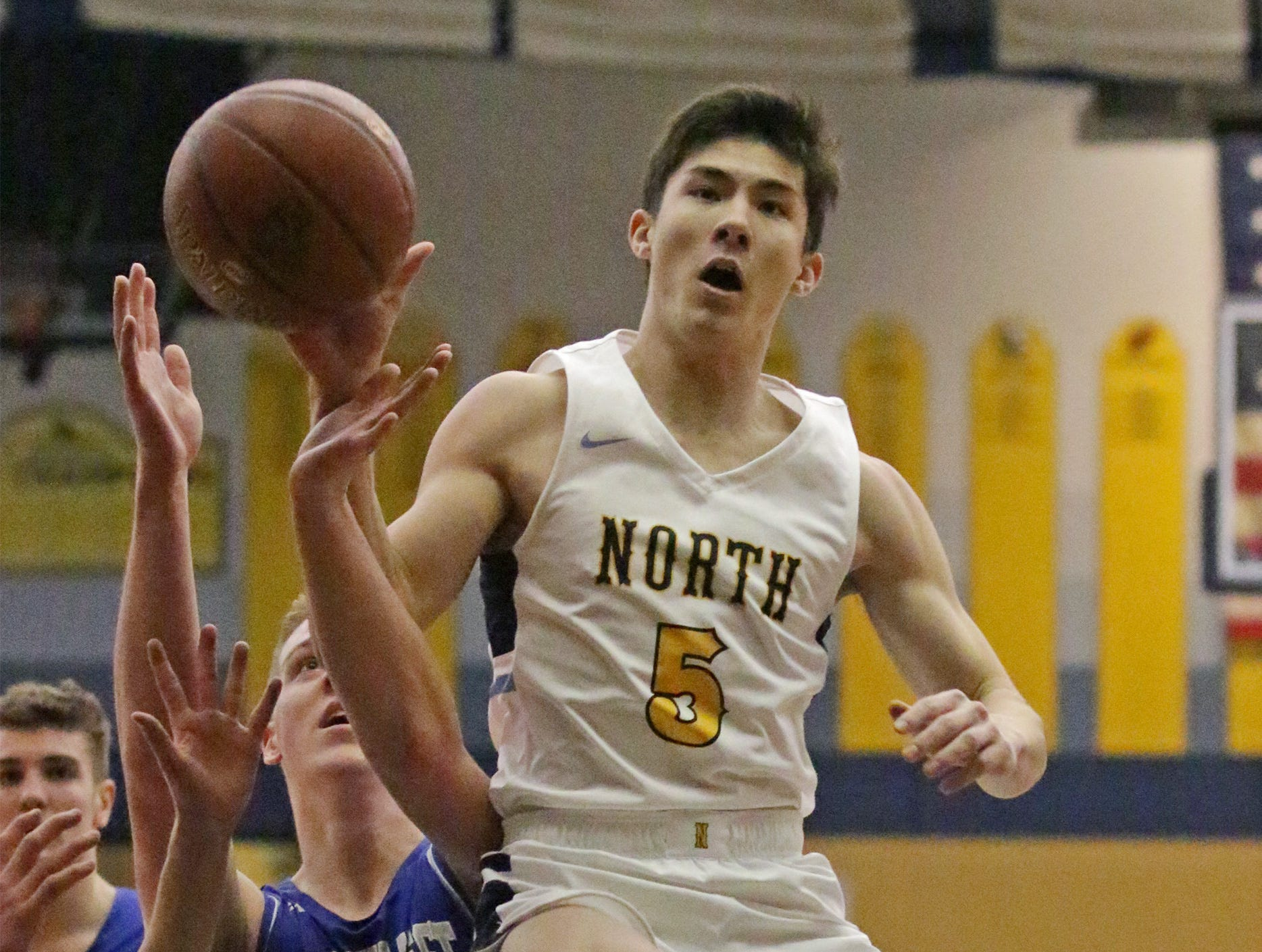 Sheboygan North's Austin Thyes (5) is airborne as he works to rebound the ball against Green Bay Southwest, Tuesday, February 5, 2019, in Sheboygan, Wis.
