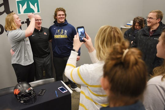 Washington's Carson Wilson, left, jokingly shines head coach Chad Stadem's head, center, for a photo during signing day Wednesday, Feb. 6, at Avera Sports Institute in Sioux Falls. Wilson singed a National Letter of Intent to play football at Augustana University.