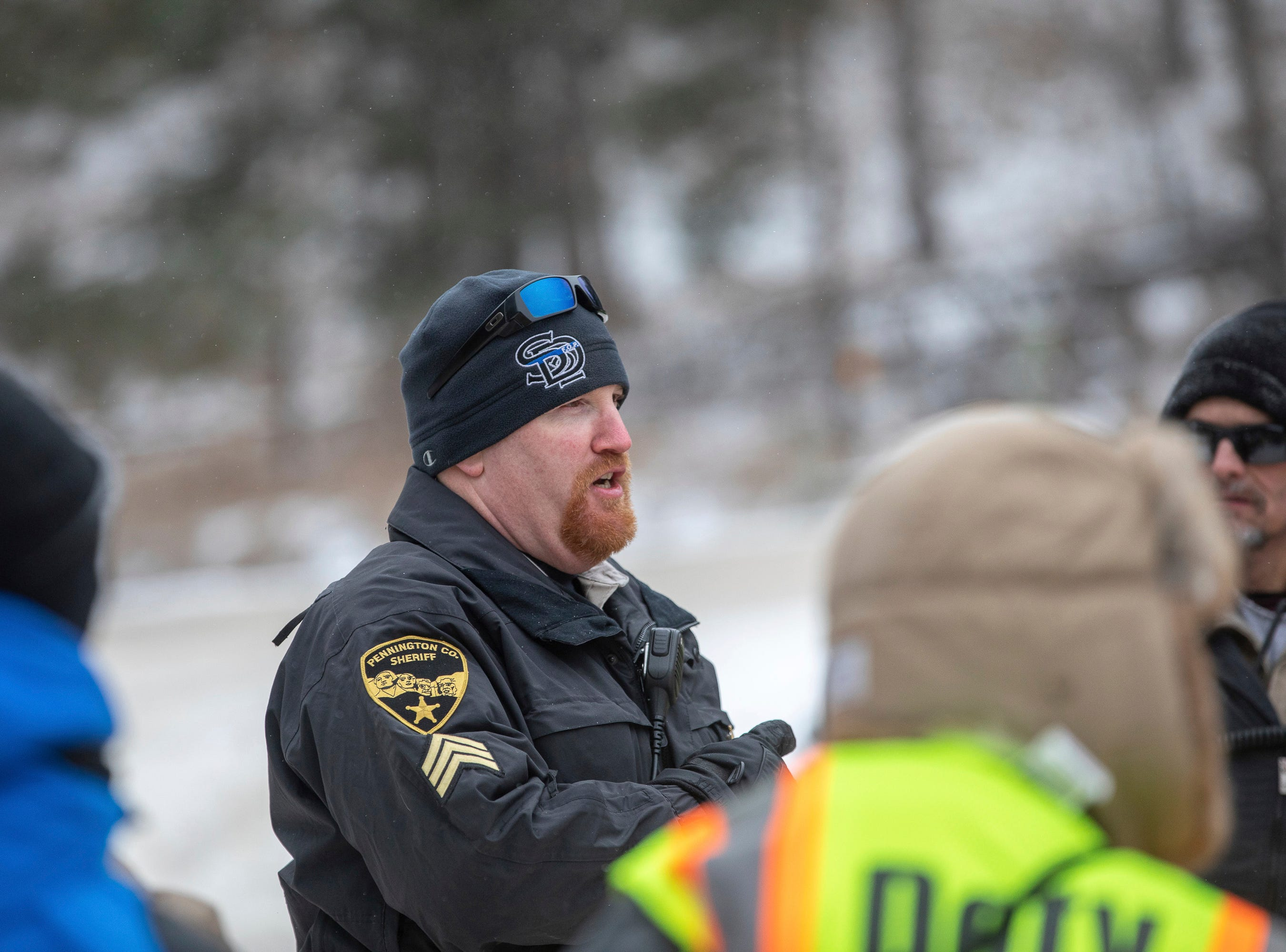 Jeromey Smith, a sergeant with the Pennington County Sheriff's Office, speaks to searchers in a parking lot at the Black Hills Children's Home near Rockerville, S.D., on Tuesday, Feb. 5, 2019, who were helping to look for Serenity Dennard, a 9-year-old girl who was last seen Sunday morning leaving the Children's Home. (Ryan Hermens/Rapid City Journal via AP)