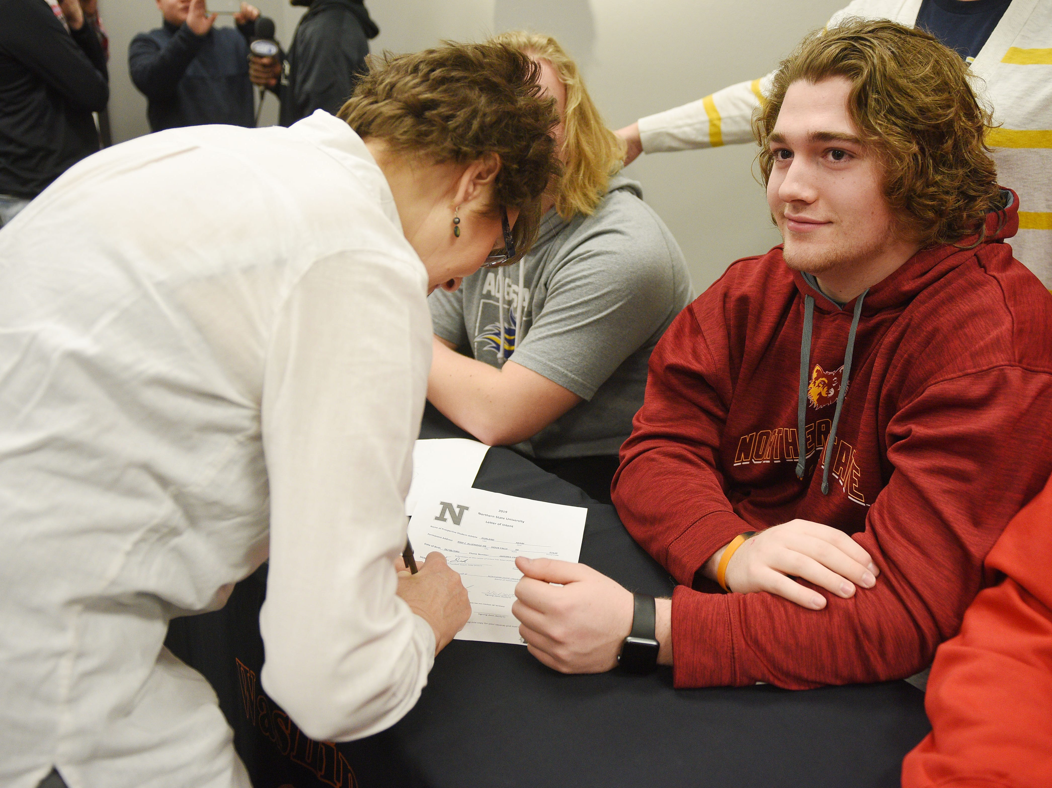 Deb Durland, left, signs her son Adam Durland's National Letter of Intent to play football at Northern State University during signing day for Washington High School Wednesday, Feb. 6, at Avera Sports Institute in Sioux Falls.