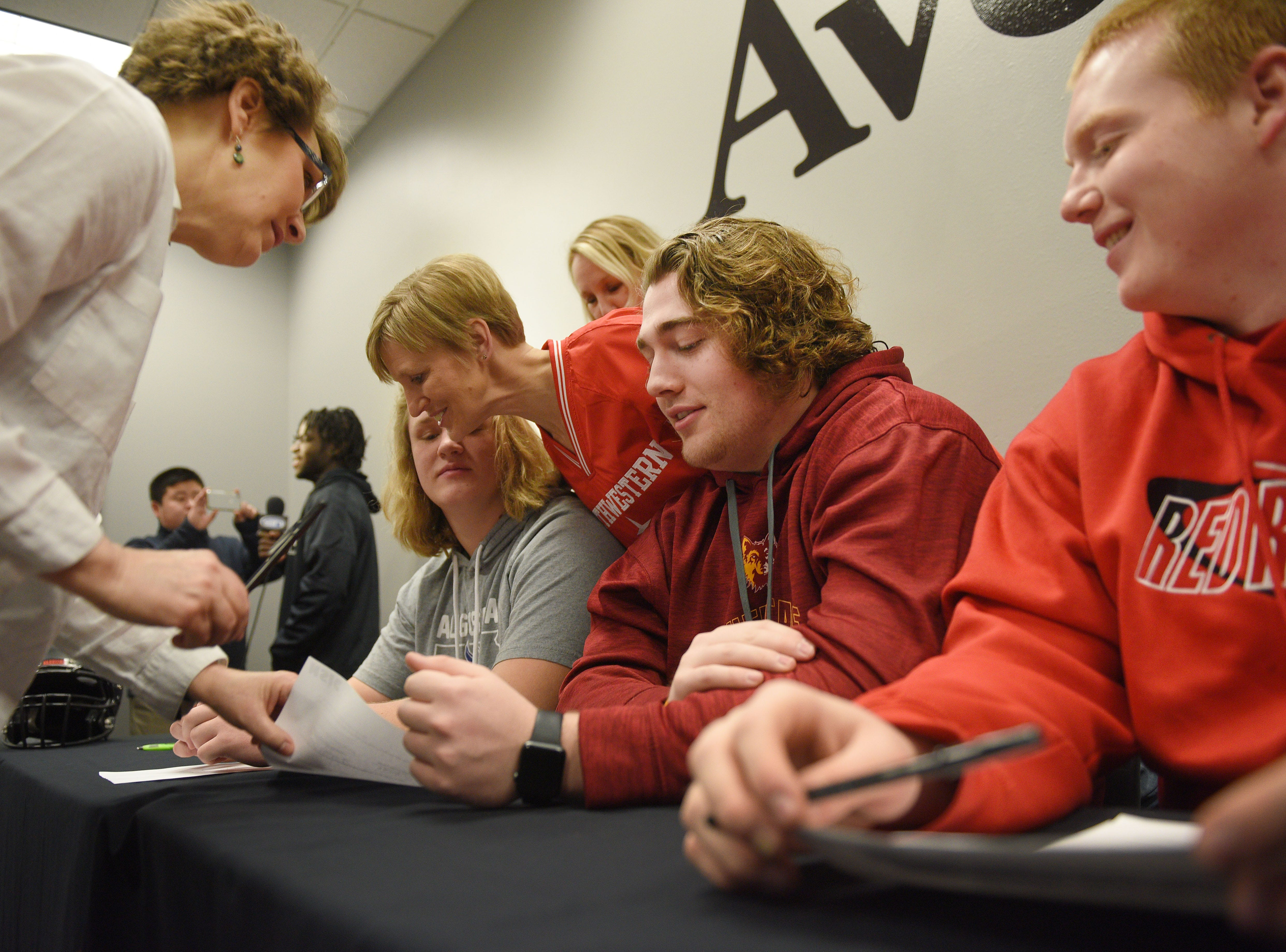 Deb Durland, far left, signs her son Adam Durland's National Letter of Intent to play football at Northern State University during signing day for Washington High School Wednesday, Feb. 6, at Avera Sports Institute in Sioux Falls.