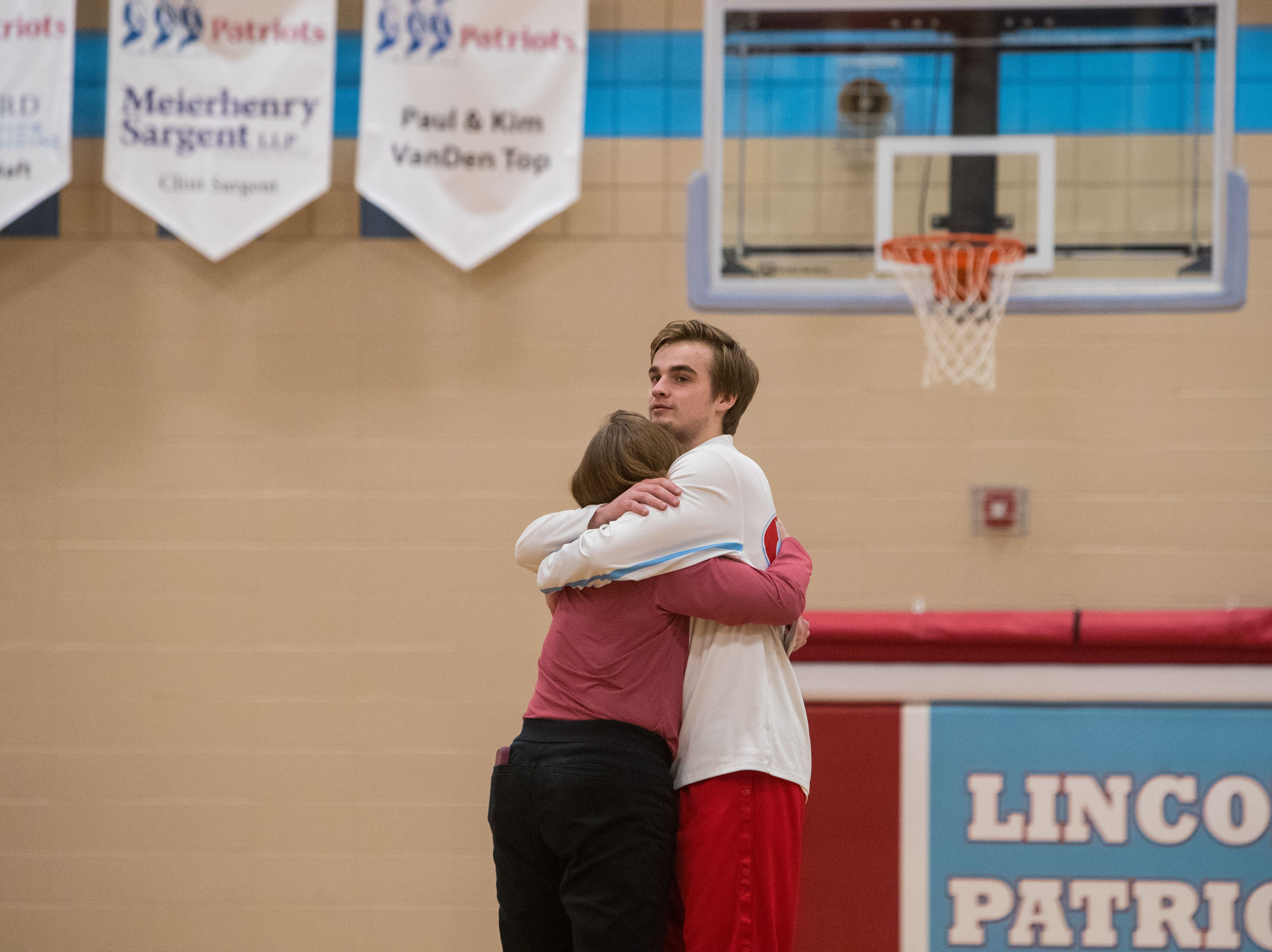 Lincoln's Nolan Ransom (21) hugs his mom, Andrea Ransom, before the game against Brandon Valley in Sioux Falls, S.D., Tuesday, Feb. 5, 2019.