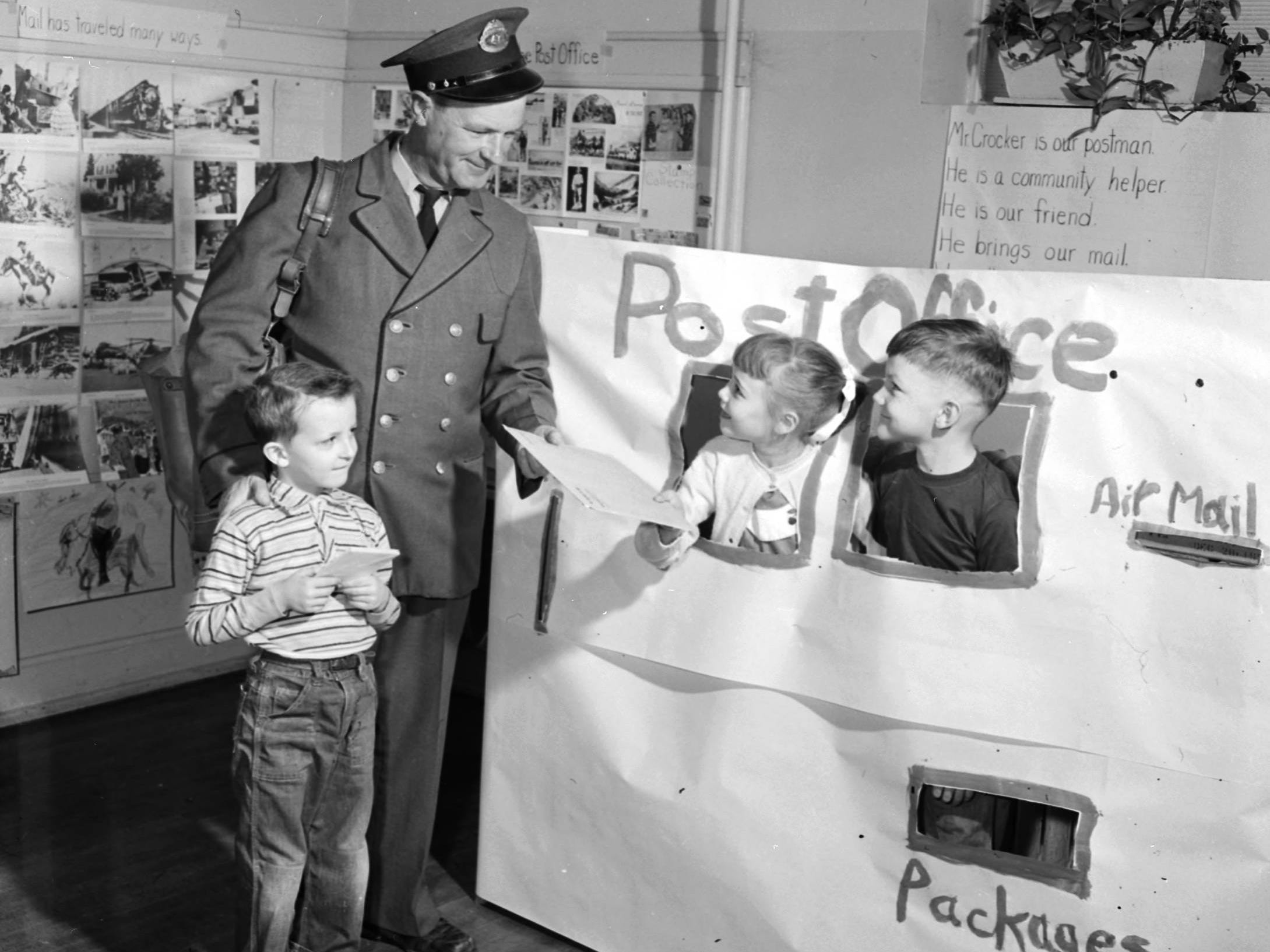 McGregor School first-graders learned about post office operations under the direction of their teacher, Miss Faye Johnson. The school's postman, Harve Crocker, is pictured with Mike Crocker, standing, Betty Kay Baker, and Richard Spahr. Published in the News & Leader on Feb. 12, 1956.