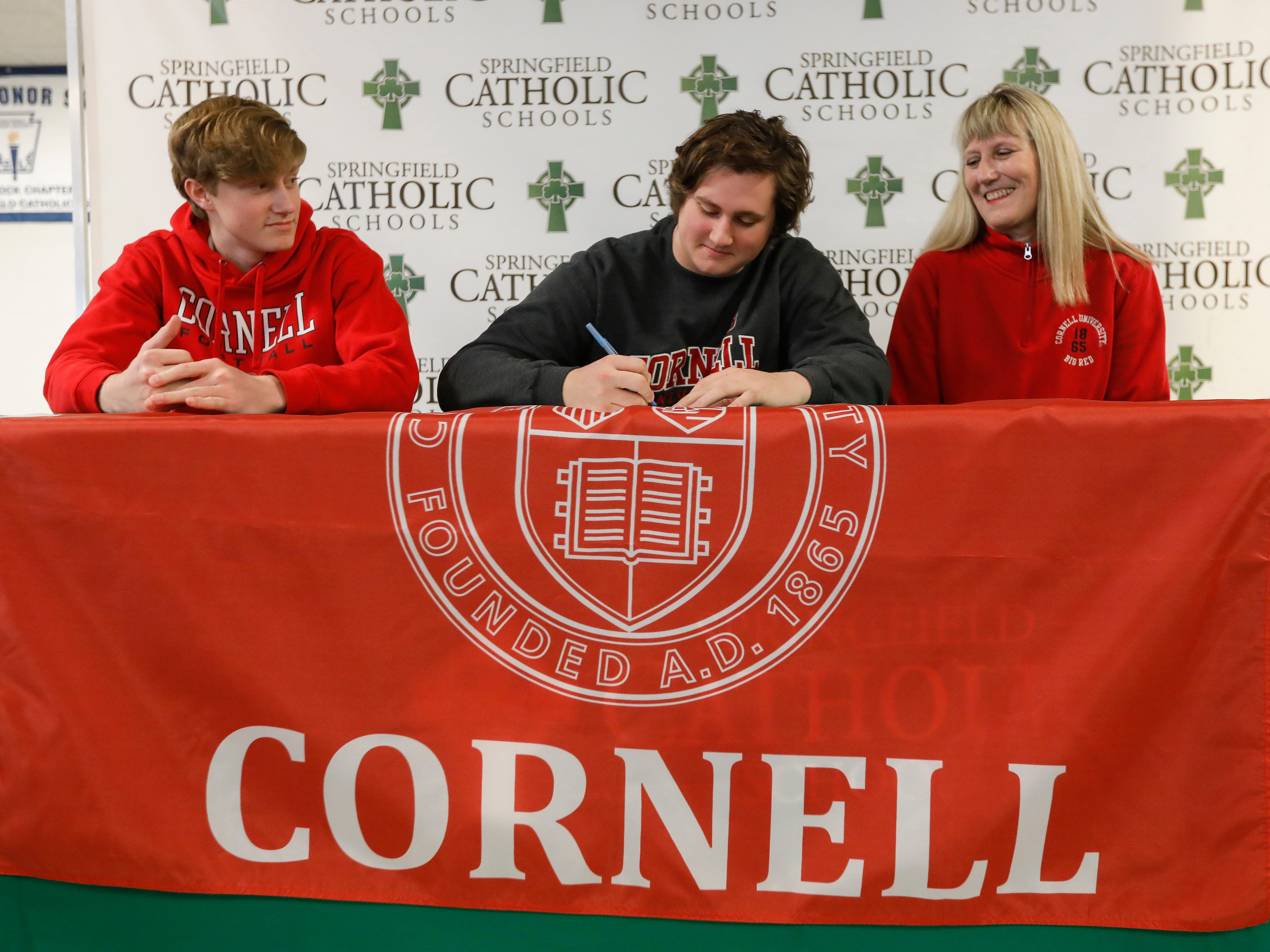 Wallace Squibb signs his letter of intent to play football at Cornell. Also pictured are his mom Amy Squibb and brother Will Squibb.