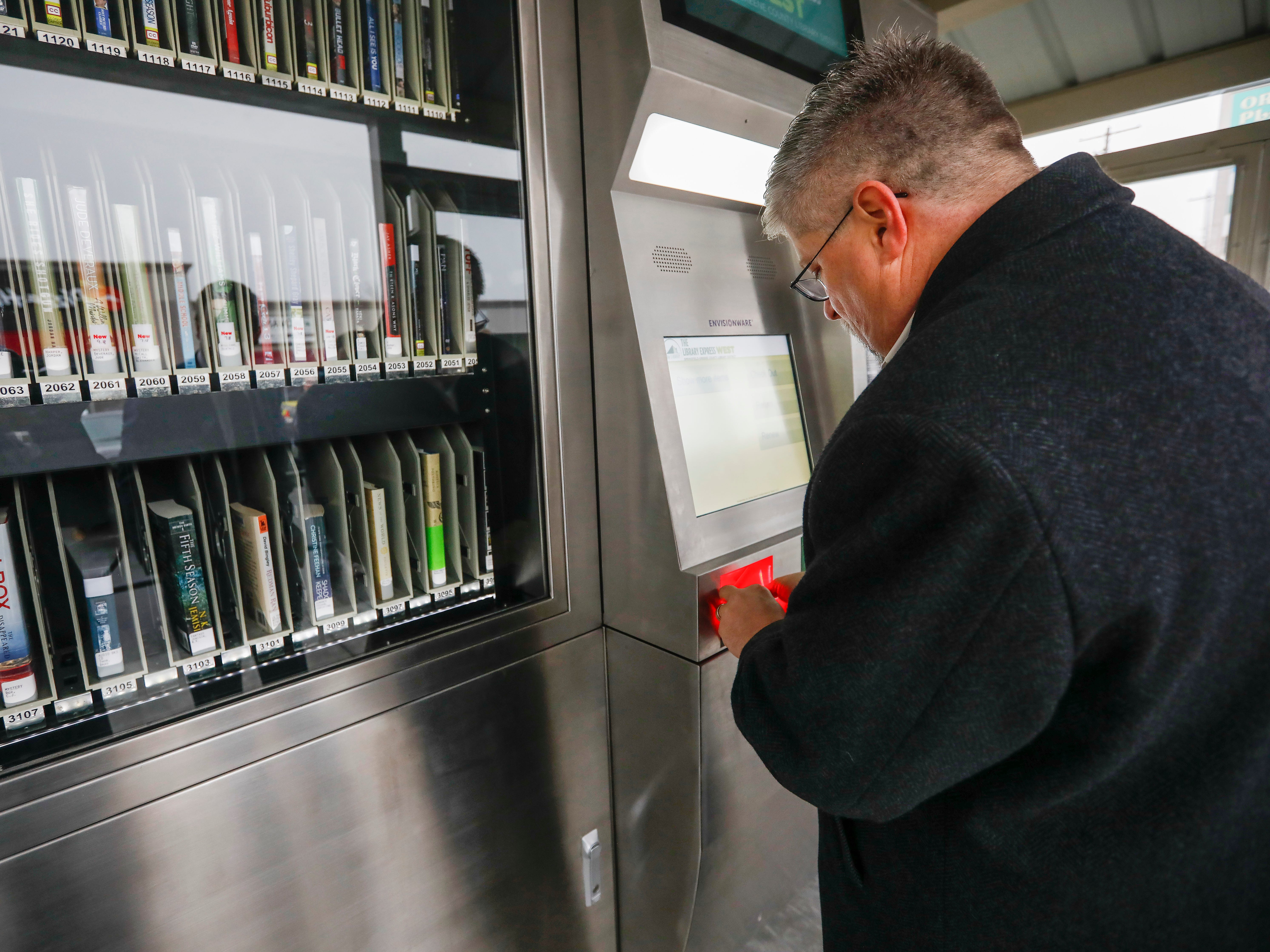 Don Chenevert, a member of the Springfield-Greene County Library Board of Trustees, scans his library card at the new Library Express West located at 3872 W. Chestnut Expressway in Orchard Plaza on Wednesday, Feb. 6, 2019.