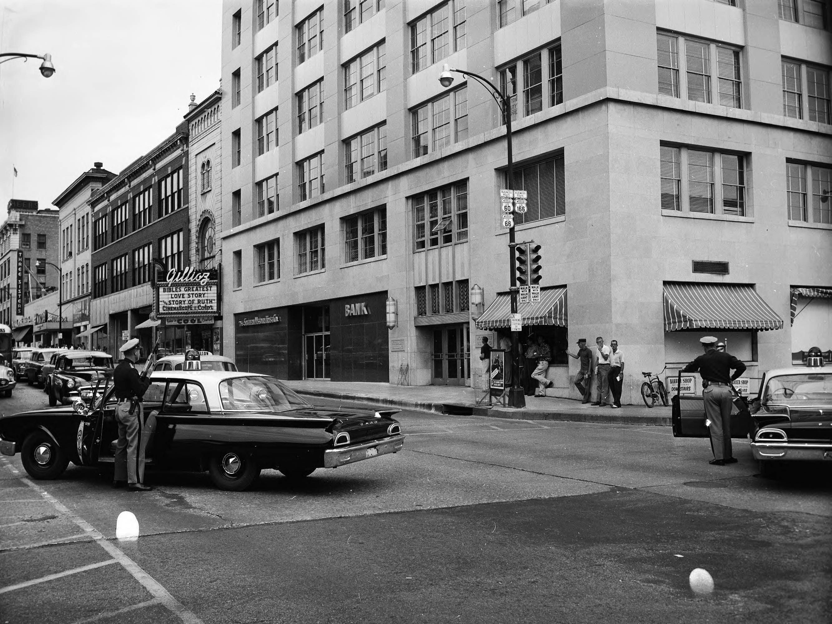 Two police cars are stopped at the corner of Jefferson and Park Central. The Woodruff building and the Gillioz are visible in the background.