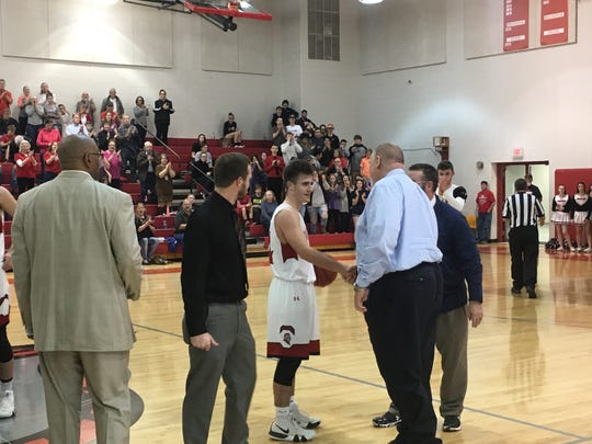 Riverheads' Grant Painter receives congratulations after scoring his 1,000th career point.