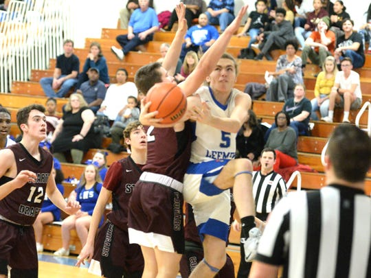 Lee High's Ethan Painter takes the ball around Stuarts Draft's Ryan Riley Tuesday night at Paul Hatcher Gym in a Shenandoah District boys basketball game.