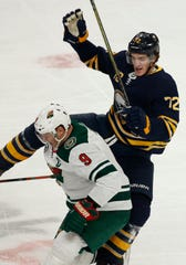 Buffalo Sabres forward Tage Thompson (72) and Minnesota Wild forward Mikko Koivu (9) collide during the first period of an NHL hockey game, Tuesday, Feb. 5, 2019, in Buffalo N.Y. (AP Photo/Jeffrey T. Barnes)