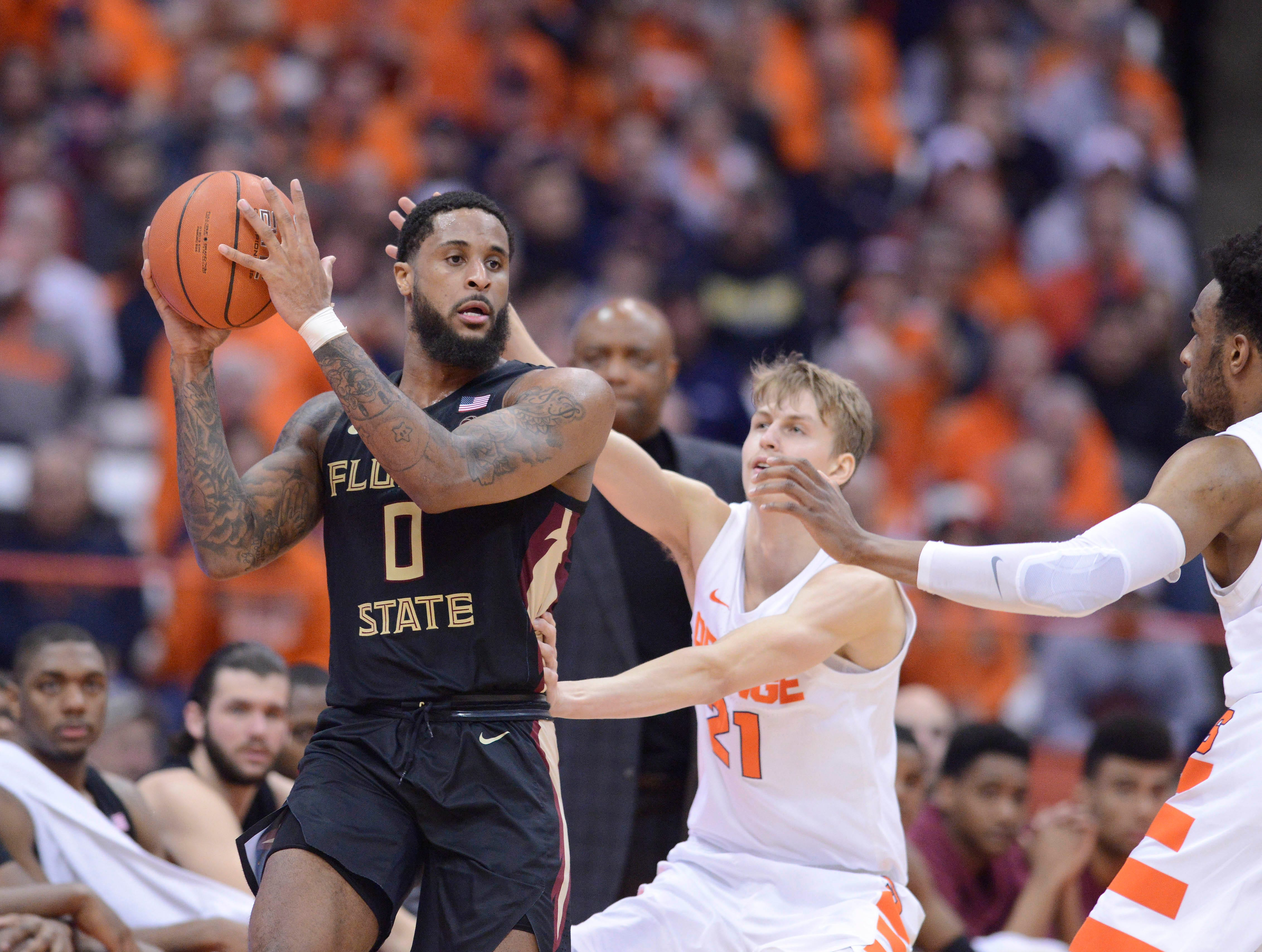 Feb 5, 2019; Syracuse, NY, USA; Florida State Seminoles forward Phil Cofer (0) controls the ball in front of Syracuse Orange forward Marek Dolezaj (21) and forward Oshae Brissett in the second half at the Carrier Dome. Mandatory Credit: Mark Konezny-USA TODAY Sports