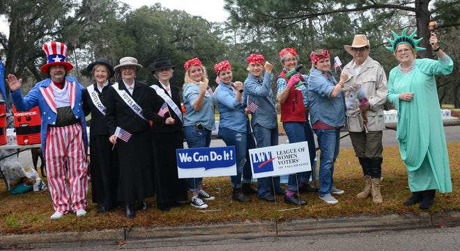 Members of the League of Women Voters of Tallahassee man the water station on Sunday during the 2019  Tallahassee Marathon. They dressed as Uncle Sam, suffragists, Rosie the Riveter, Teddy Roosevelt and Lady Liberty.